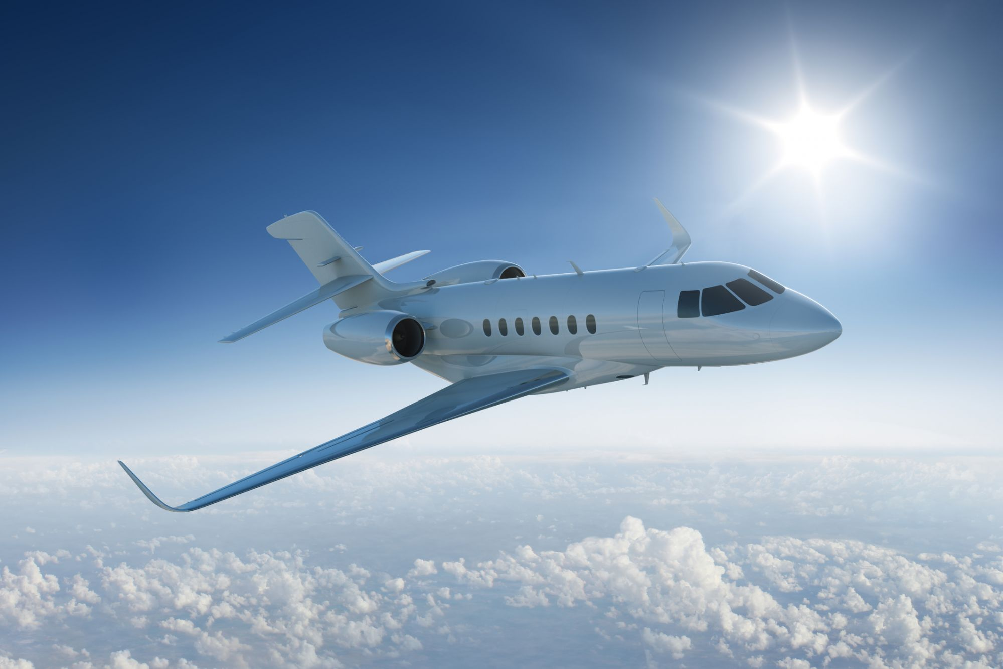 Private jet flies past sun - in blue sky above the clouds