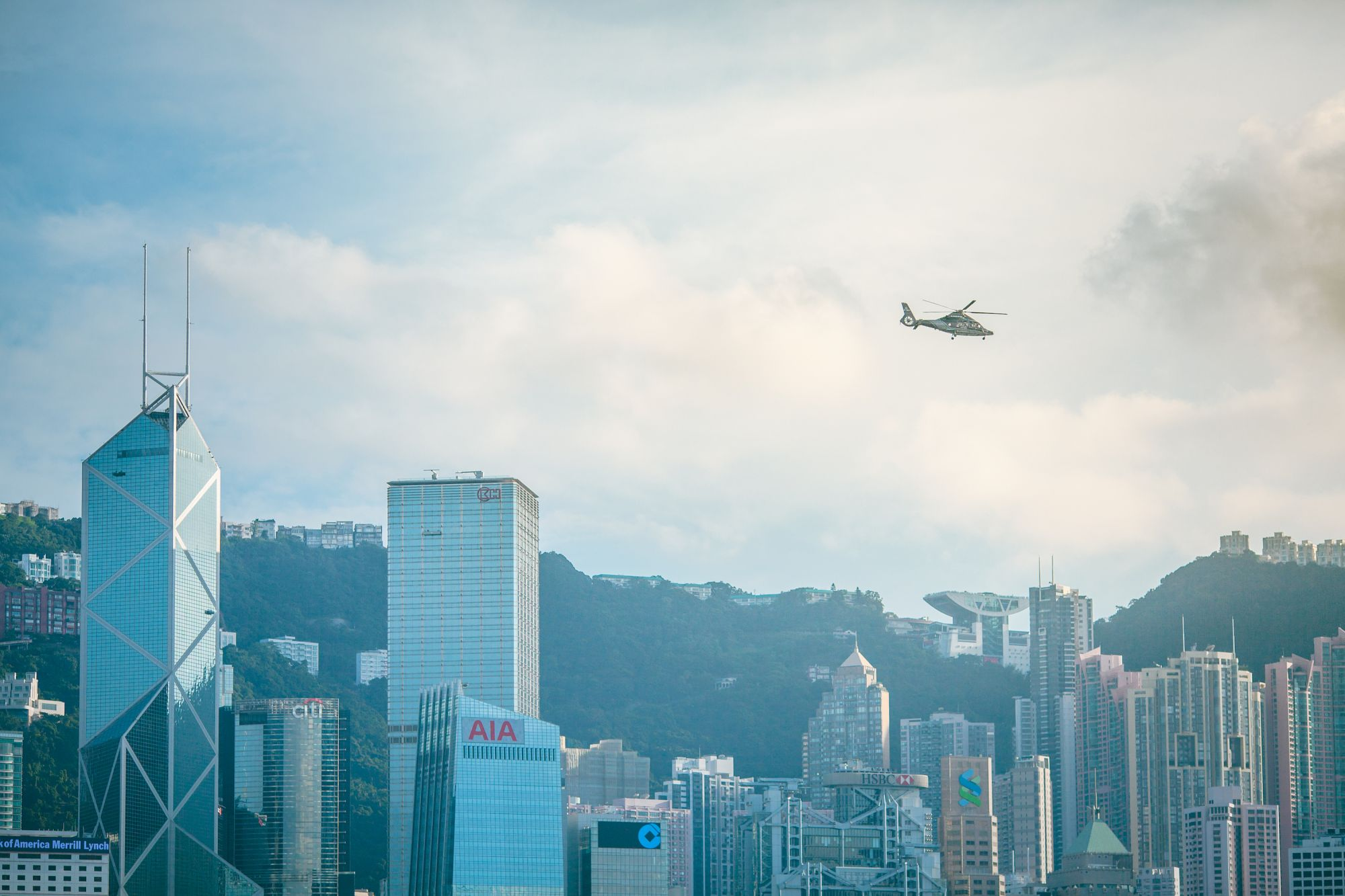 Helicopter flying over Hong Kong city skyline on a bright clear day.