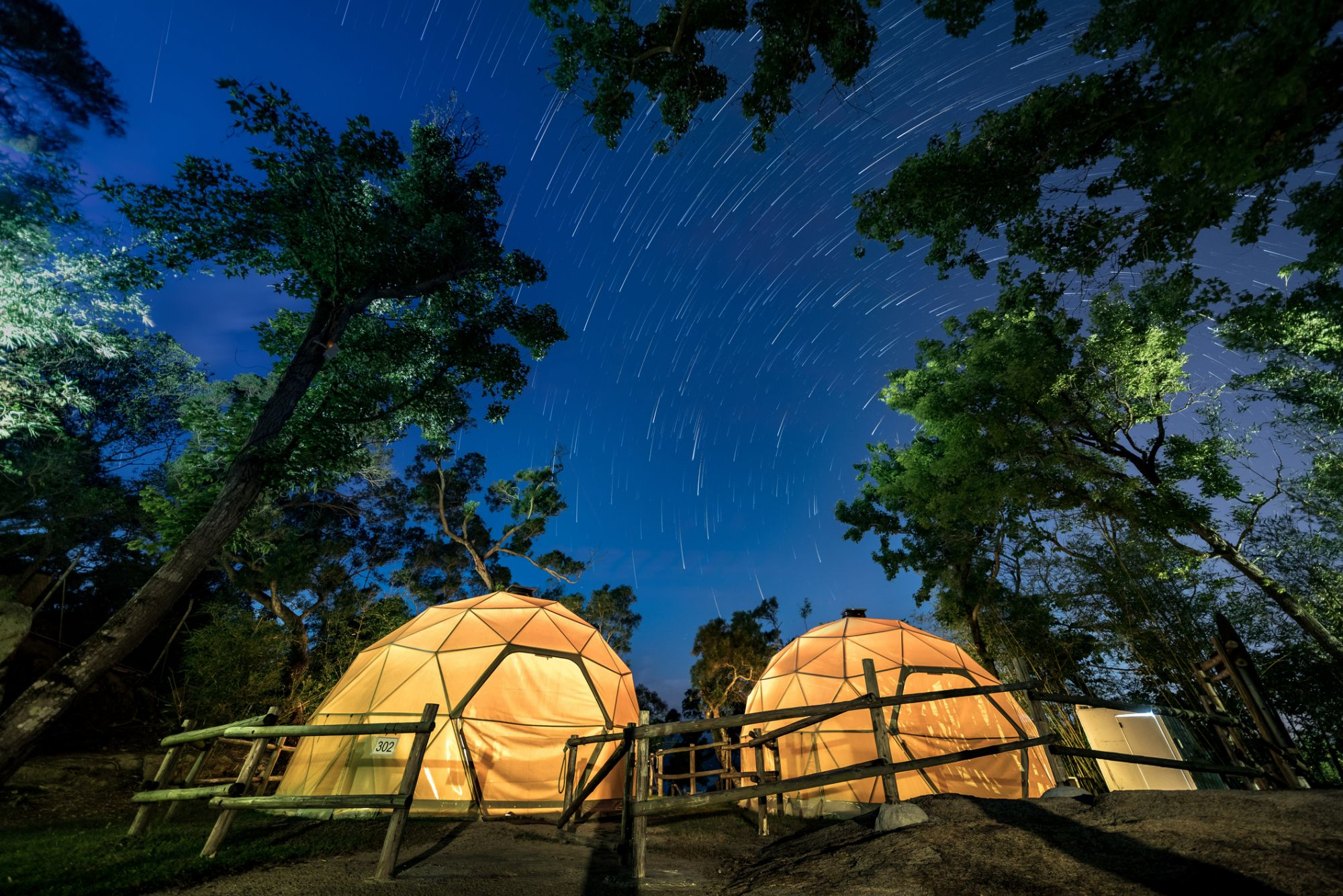 night sky with star trails over 2 dume tents