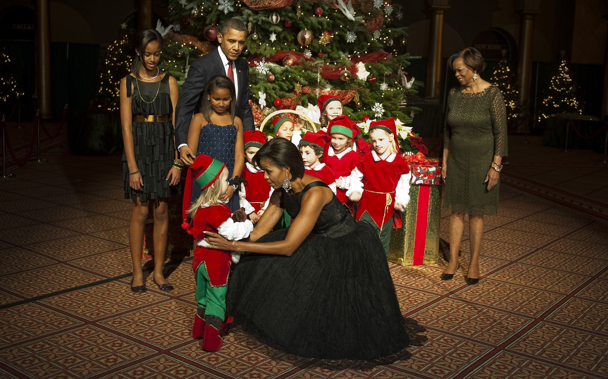 First Lady Michelle Obama (C) picks up Meghan Maurano as US President Barack Obama (3rd L) poses with children dressed as Santa's elves, his mohter-in-law Marian Robinson (R) and his two daughters Malia (L) and Sasha (2nd L) watch during a reception for Christmas in Washington, a charitable fundraiser and musical celebration of the holidays, at the National Building Museum in Washington, DC, December 12, 2010. AFP PHOTO/Jim WATSON (Photo credit should read JIM WATSON/AFP via Getty Images)