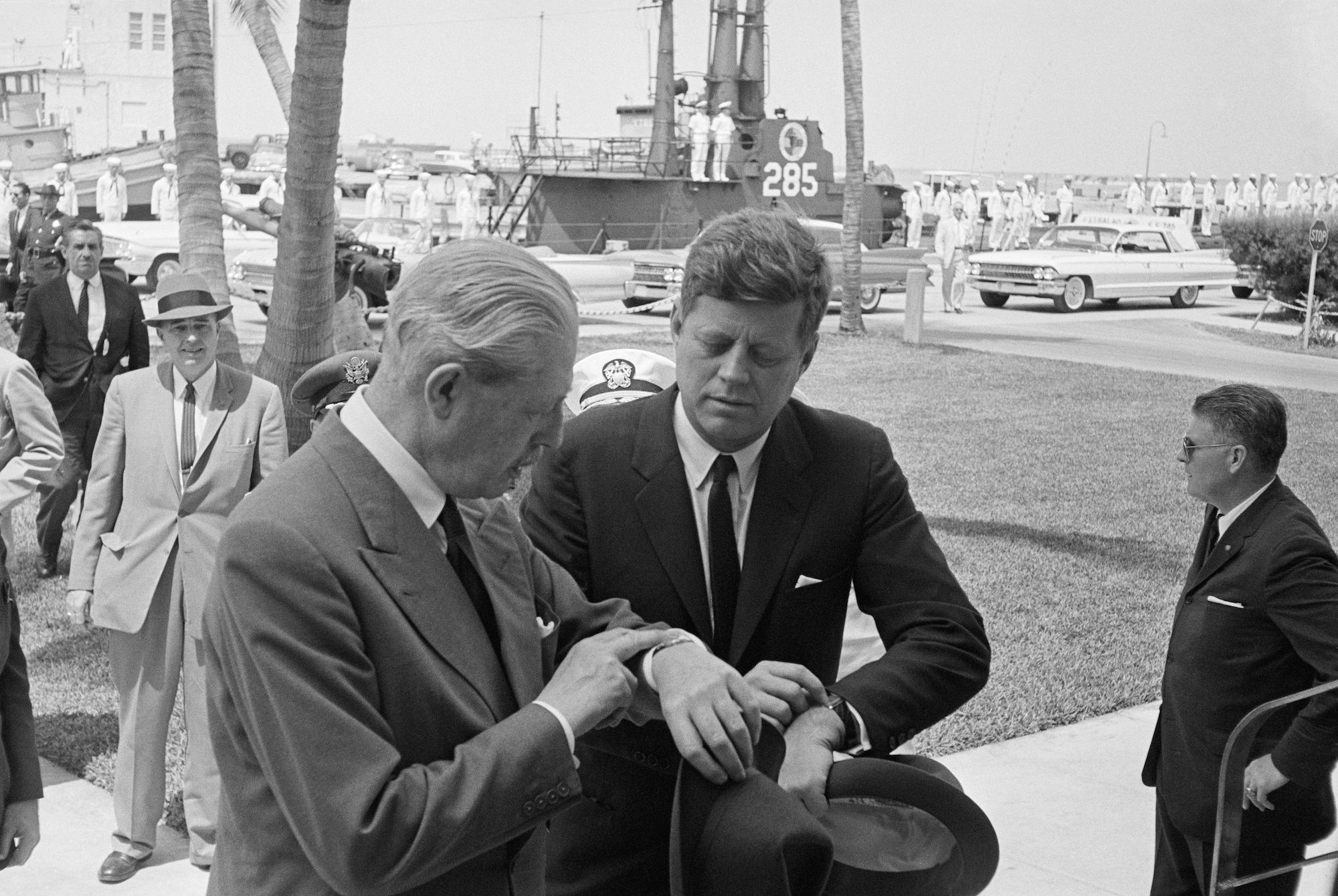 (Original Caption) Kennedy and Macmillan Sync Watches. Key West, Fla.: President Kennedy and British Prime Minister Harold Macmillan synchronize their watches as they part outside the Administration Building at the Naval Base here after arrival today. The Prime Minister went to a meeting room in the Administration Building, but the Chief Executive went to the Little White House on the base. They meet later today on the Laos crisis.
