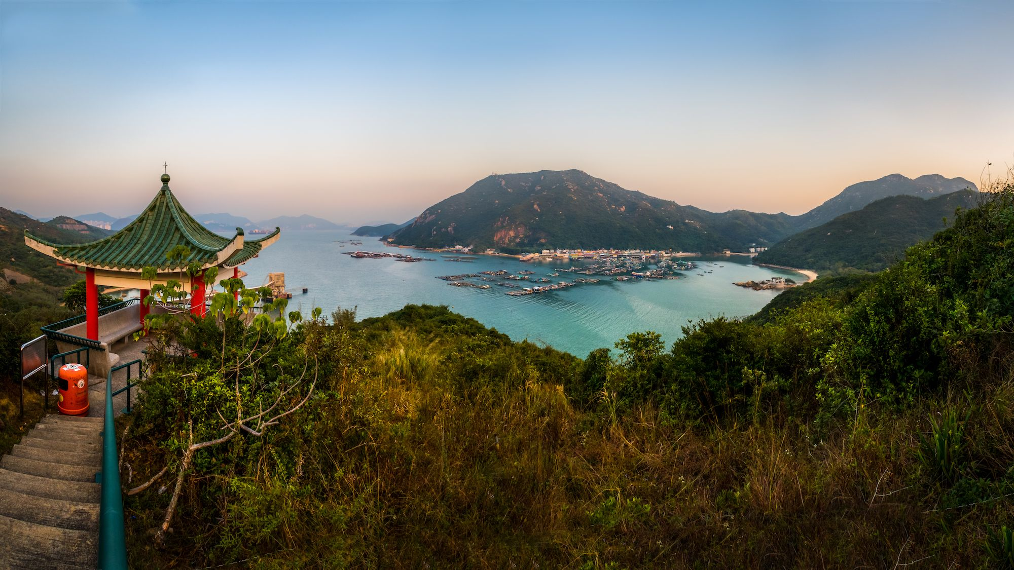 A scenic and tranquil panoramic view of Sok Kwu Wan, Lamma island from along the walking trail during sunset. Sok Kwu Wan is popular and known as a fishing village town and famous tourist attraction with lots of seafood restaurants on the island, Hong Kong - China.
