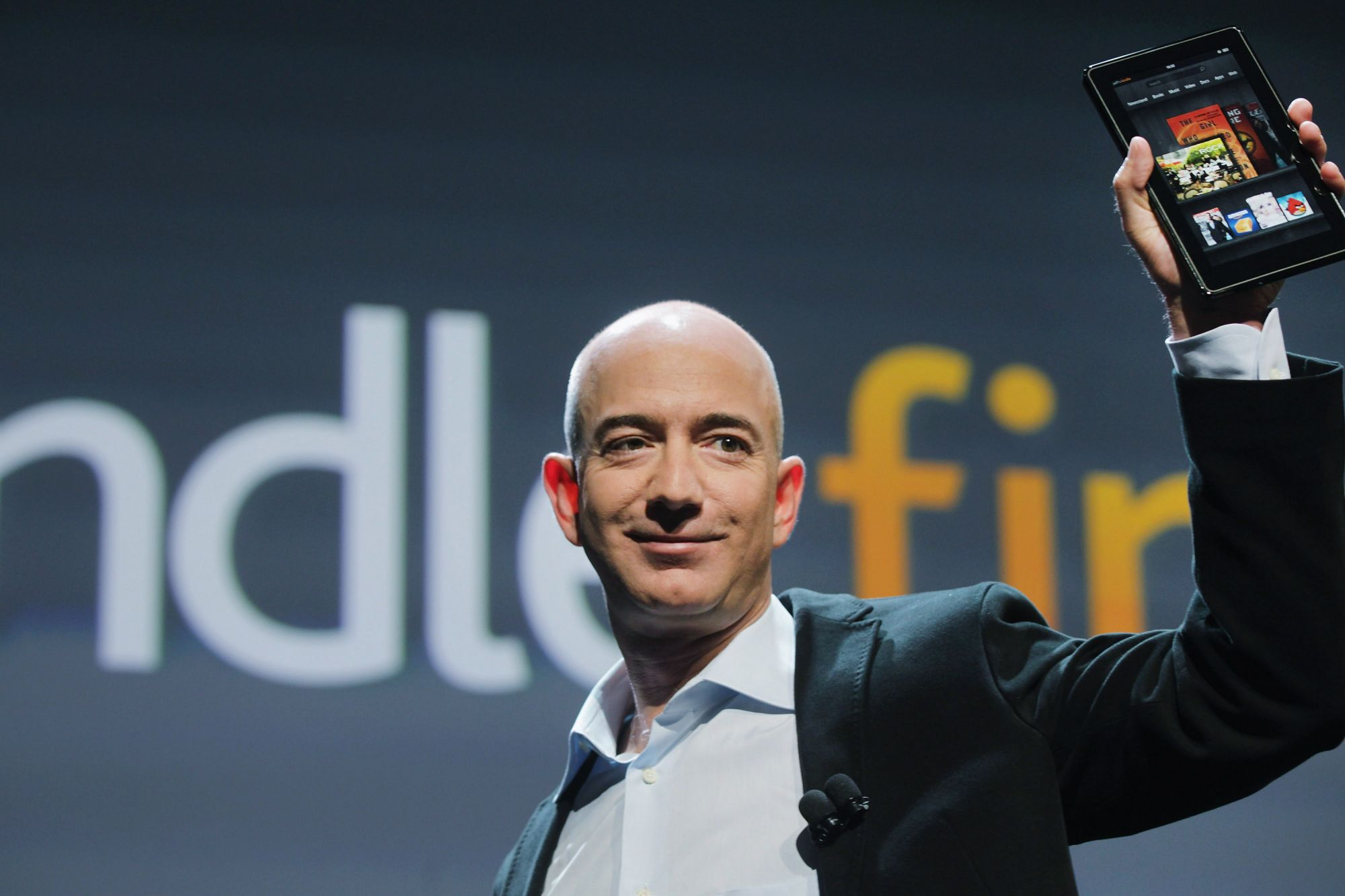 NEW YORK, NY - SEPTEMBER 28:  Amazon founder Jeff Bezos holds the new Amazon tablet called the Kindle Fire on September 28, 2011 in New York City. The Fire, which will be priced at $199, is an expanded version of the company's Kindle e-reader that has 8GB of storage and WiFi. The Fire gives users access to streaming video, as well as e-books, apps and music, and has a Web browser. In addition to the Fire, Bezos introduced four new Kindles including a Kindle touch model.  (Photo by Spencer Platt/Getty Imag