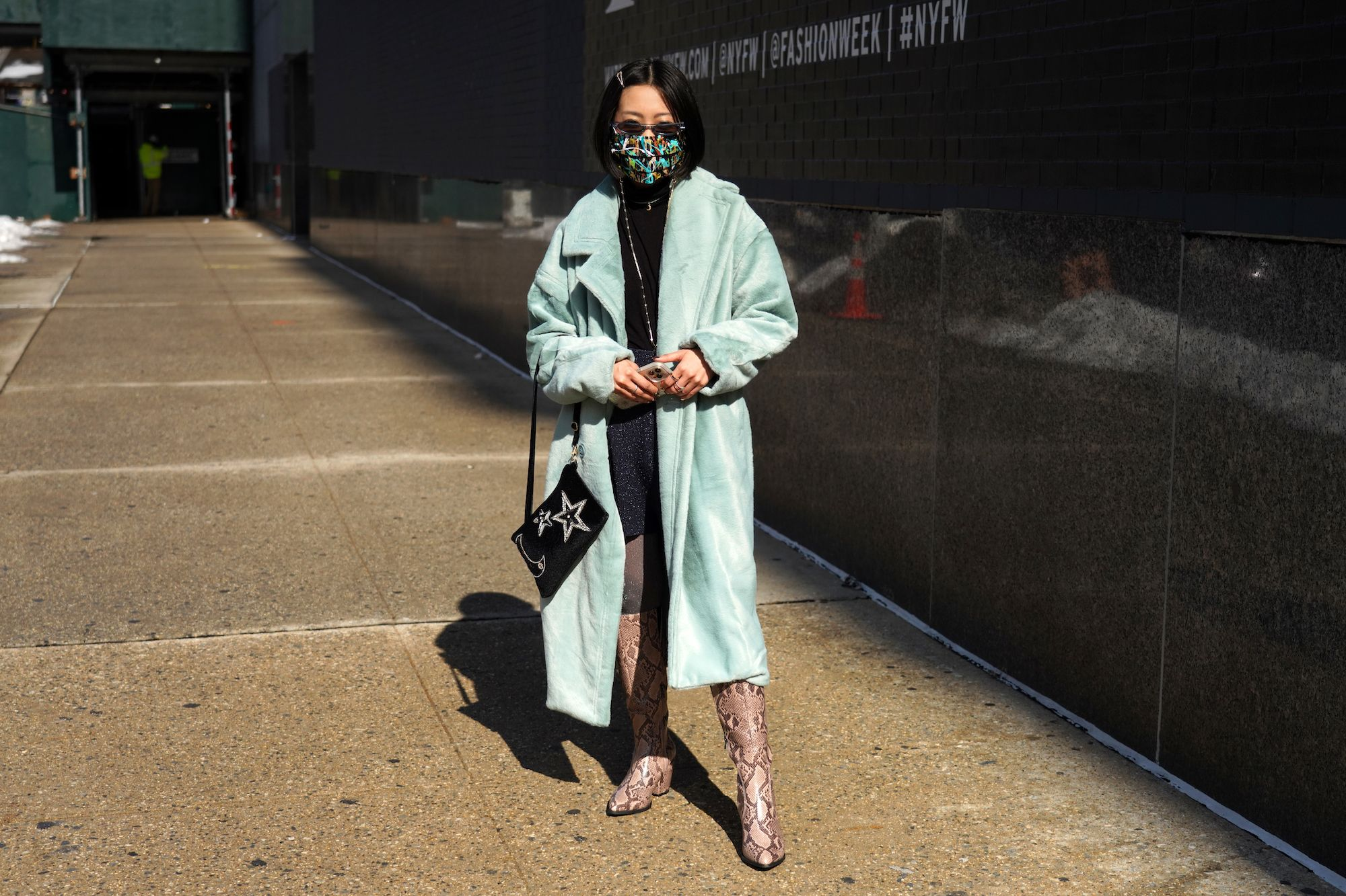 A guest wearing a pale blue coat and tan snakeskin boots carries a black velvet handbag with sequined moon and stars during New York Fashion Week: The Shows at Spring Studios on February 16, 2021 in New York City. (Image: Cindy Ord/Getty Images)