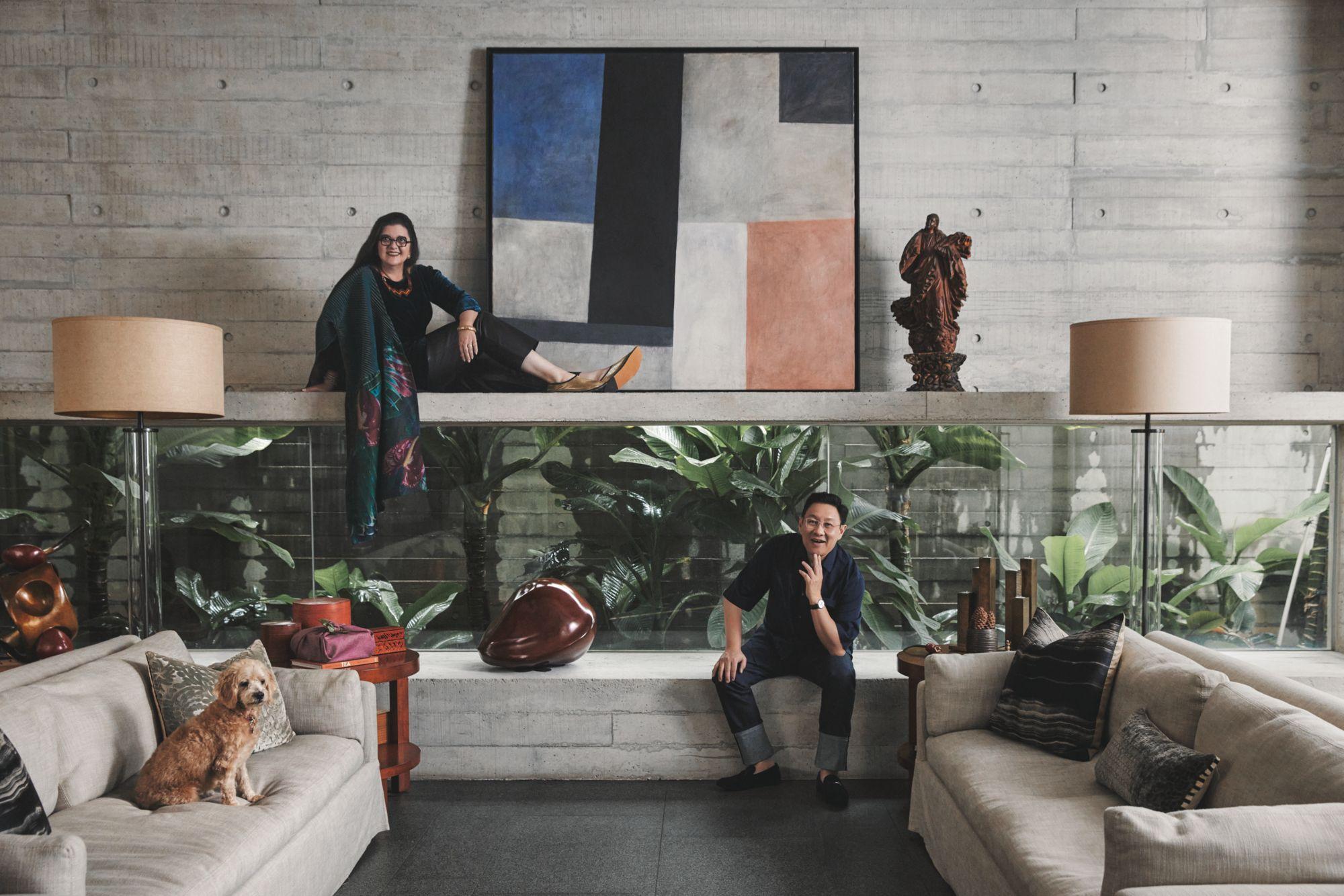 夫妻倆和愛犬Biggles攝於客廳,這裡設計了一處長長的凹室,鑲上大面水平玻璃窗,把戶外植物給框了進來。房裡也擺設了許多種籽雕像。黃超文腕錶by Piaget。(Photo: Darren Gabriel Leow for Tatler Hong Kong)