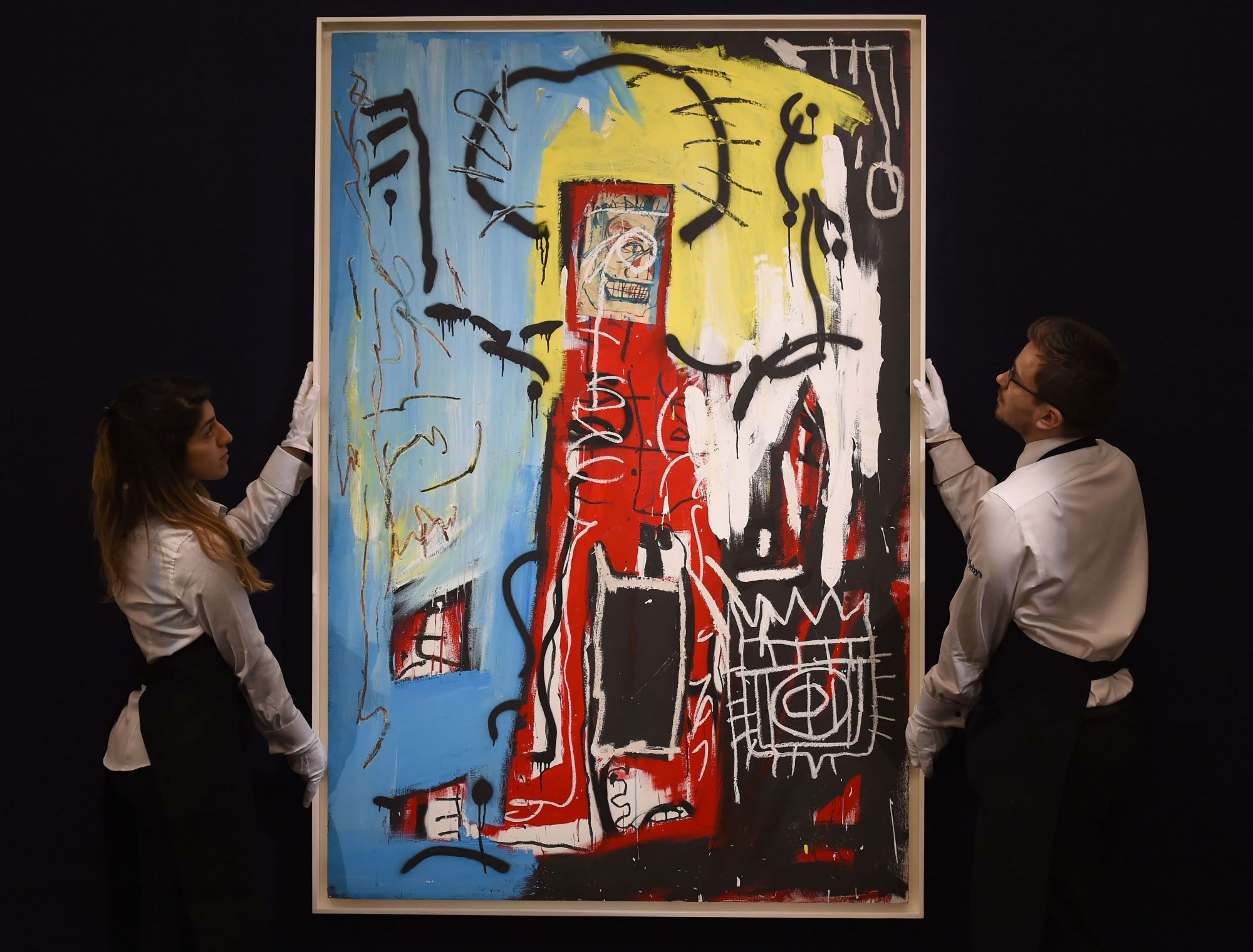 Sotheby's employees adjust Untitled (One Eyed Man or Xerox Face) painted in 1982 by Jean-Michel Basquiat which is estimated to fetch £14,000,000 - 18,000,000 at auction as part of their forthcoming sales of impressionist, modern, surrealist and contemporary art, together estimated to reach over £360 million. (Photo by Charlotte Ball/PA Images via Getty Images)