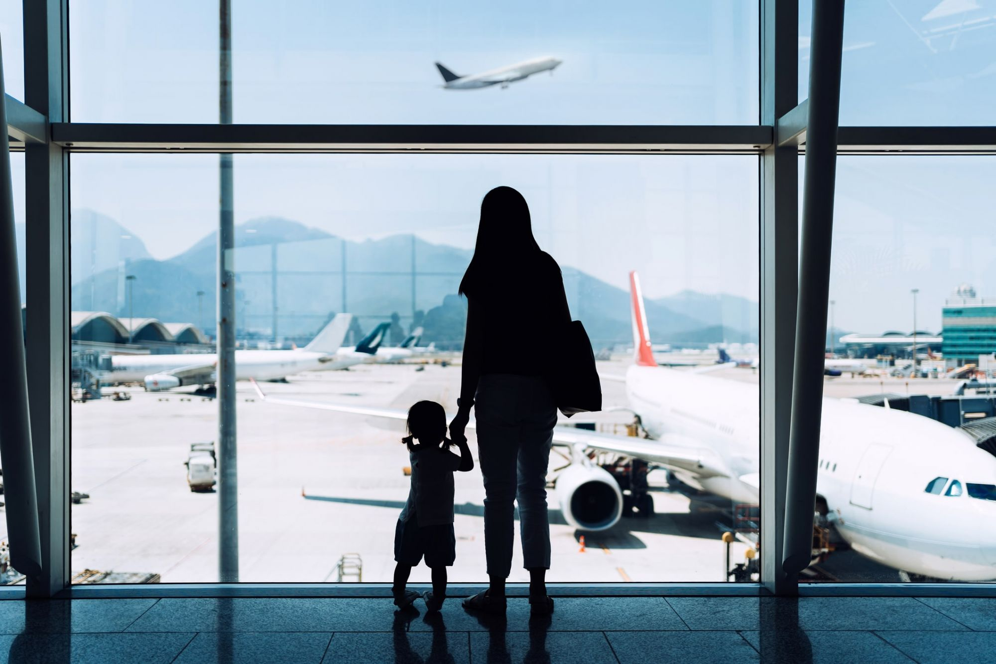 woman and child look out on hong kong airport plane taking off