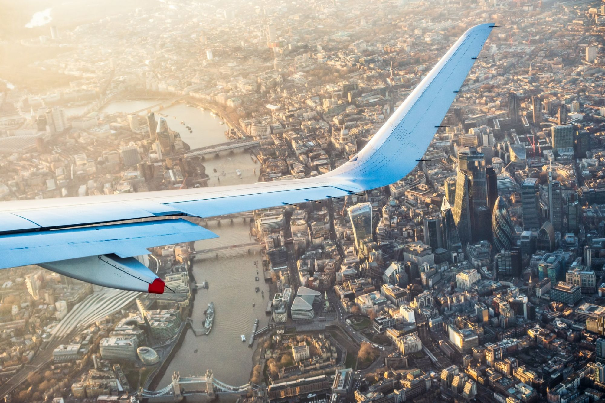 Wing of plane flying over London at golden hour