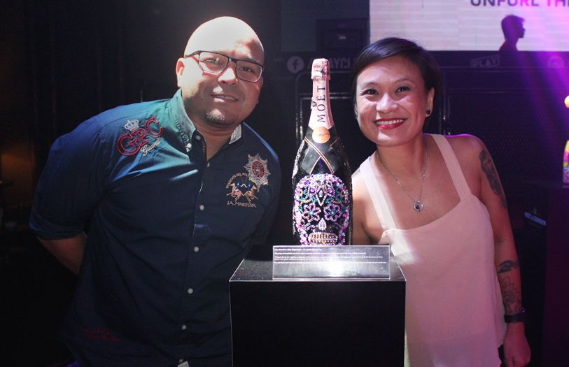 Keith Raymond and Lina David with Lina's bottle design, which was inspired by the sugar skull motif of Mexico.