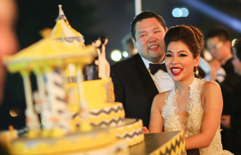 Benjamin Yong and Elizabeth Lee cutting their carnival-themed wedding cake.