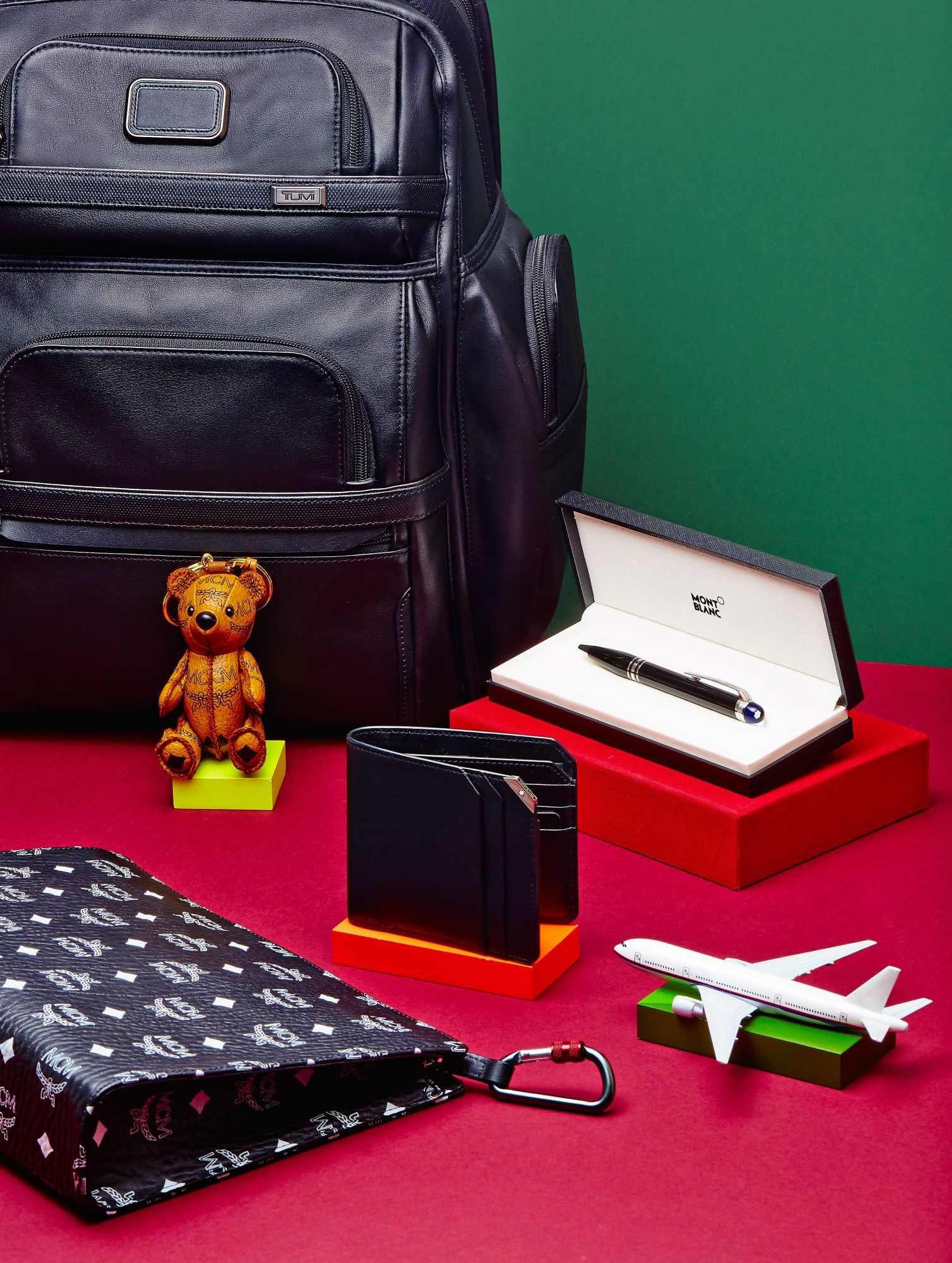 Alpha 3 Business Class Brief Pack, at Tumi; Teddy bear and clutch, at MCM;  Meisterstück Urban wallet and pen, at Montblanc