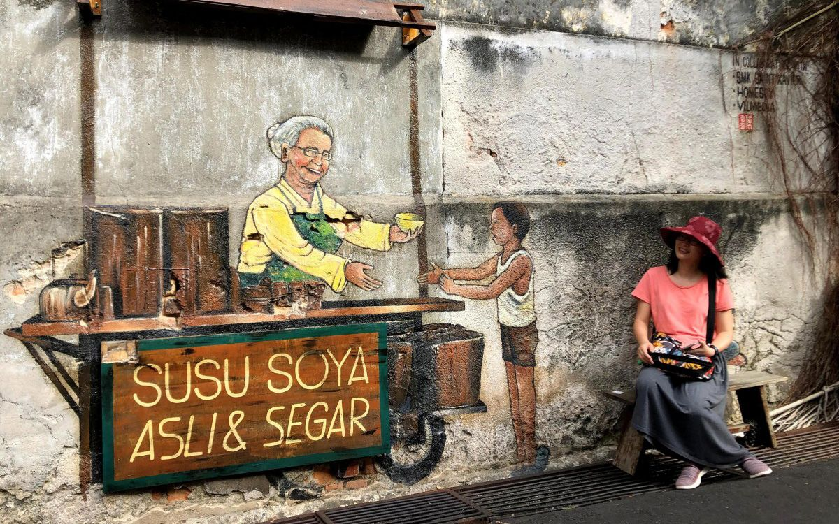 A tourist posing with a mural in Georgetown, Penang. Photo: Chung Kevin