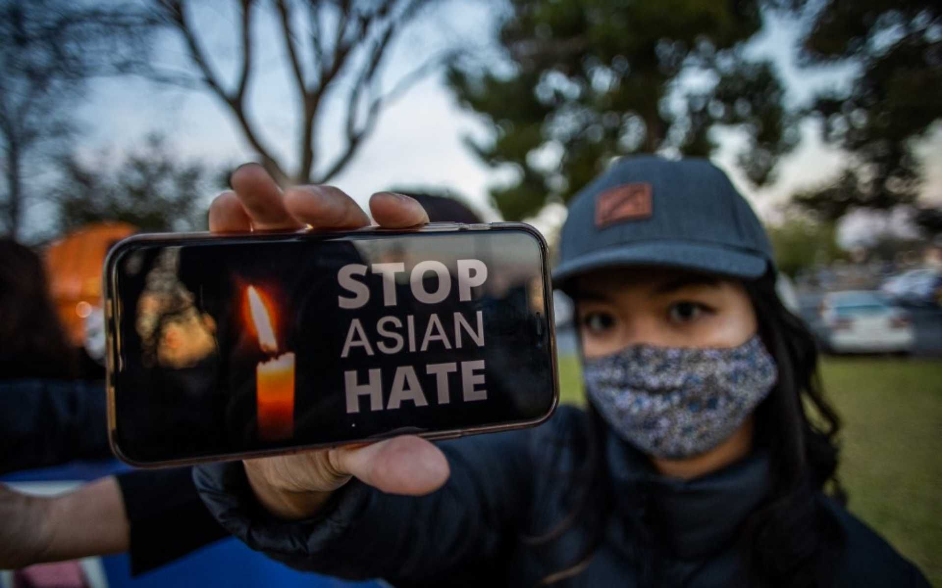 Julie Tran holds her phone during a candlelight vigil in Garden Grove, California, on March 17, 2021 to unite against the recent spate of violence targeting Asians and to express grief and outrage after yesterday's shooting that left eight people dead in Atlanta, Georgia, including at least six Asian women. - Police have said suspect Robert Aaron Long, a 21-year-old white man, has so far denied a racist motive for the three shootings in the southern US state of Georgia. (Photo by Apu GOMES / AFP)