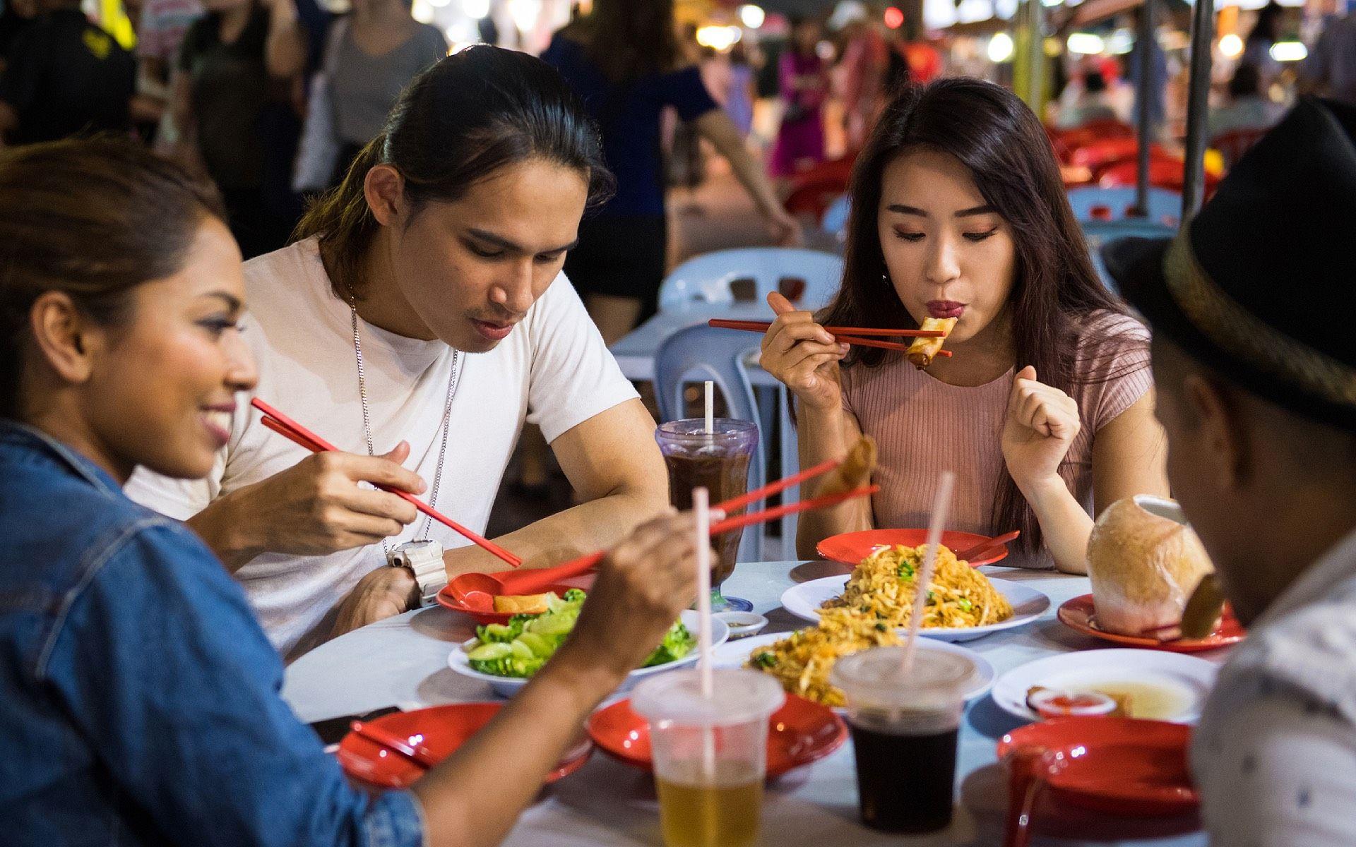 Friends tucking into street eats at Jalan Alor, Kuala Lumpur (Photo: iStock)