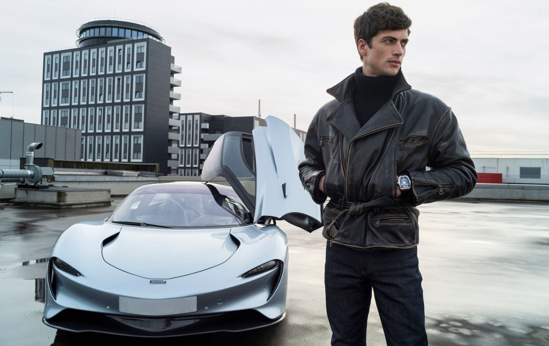 A model wearing the Richard Mille watch posing against the McLaren Speedtail supercar