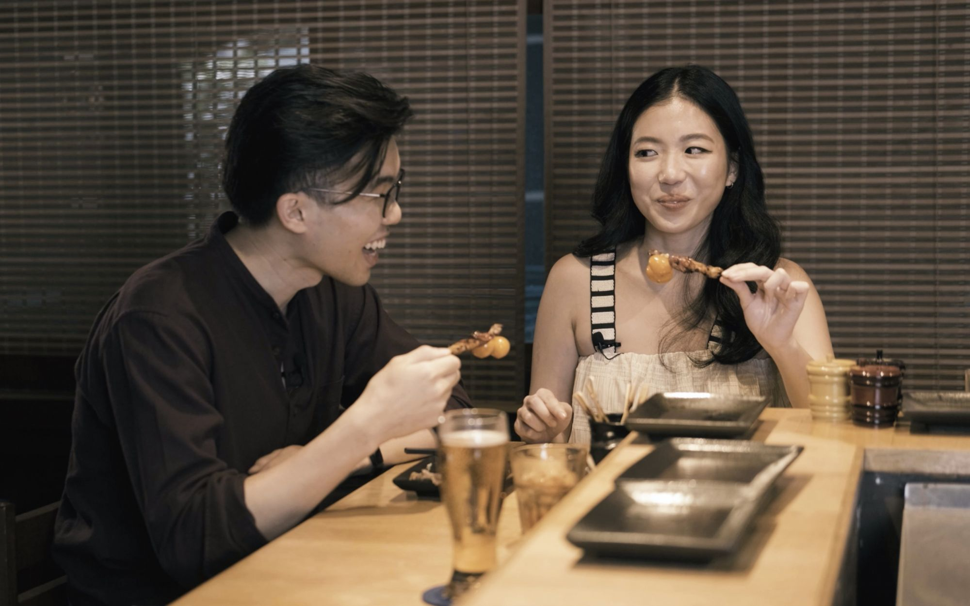 """You first."" Food podcaster Loh Yi Jun and Tatler dining editor Samantha Lim take on chicken ovaries at Toritama"