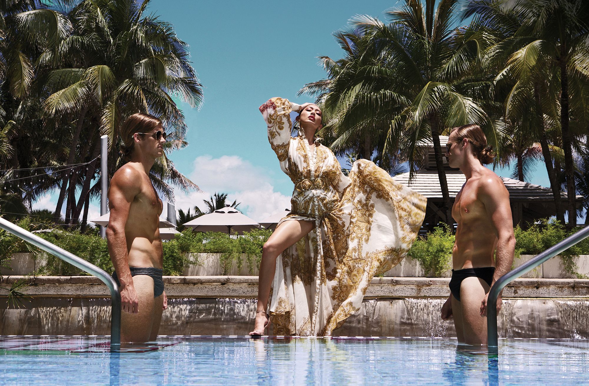 (On Alyssa) Gold and white caftan dress by Zimmerman, gold sandals by Guiseppe Zanotti, and accessories by Cristina Sabatini; (on male models) Trunks by Speedo and sunglasses by Carrera