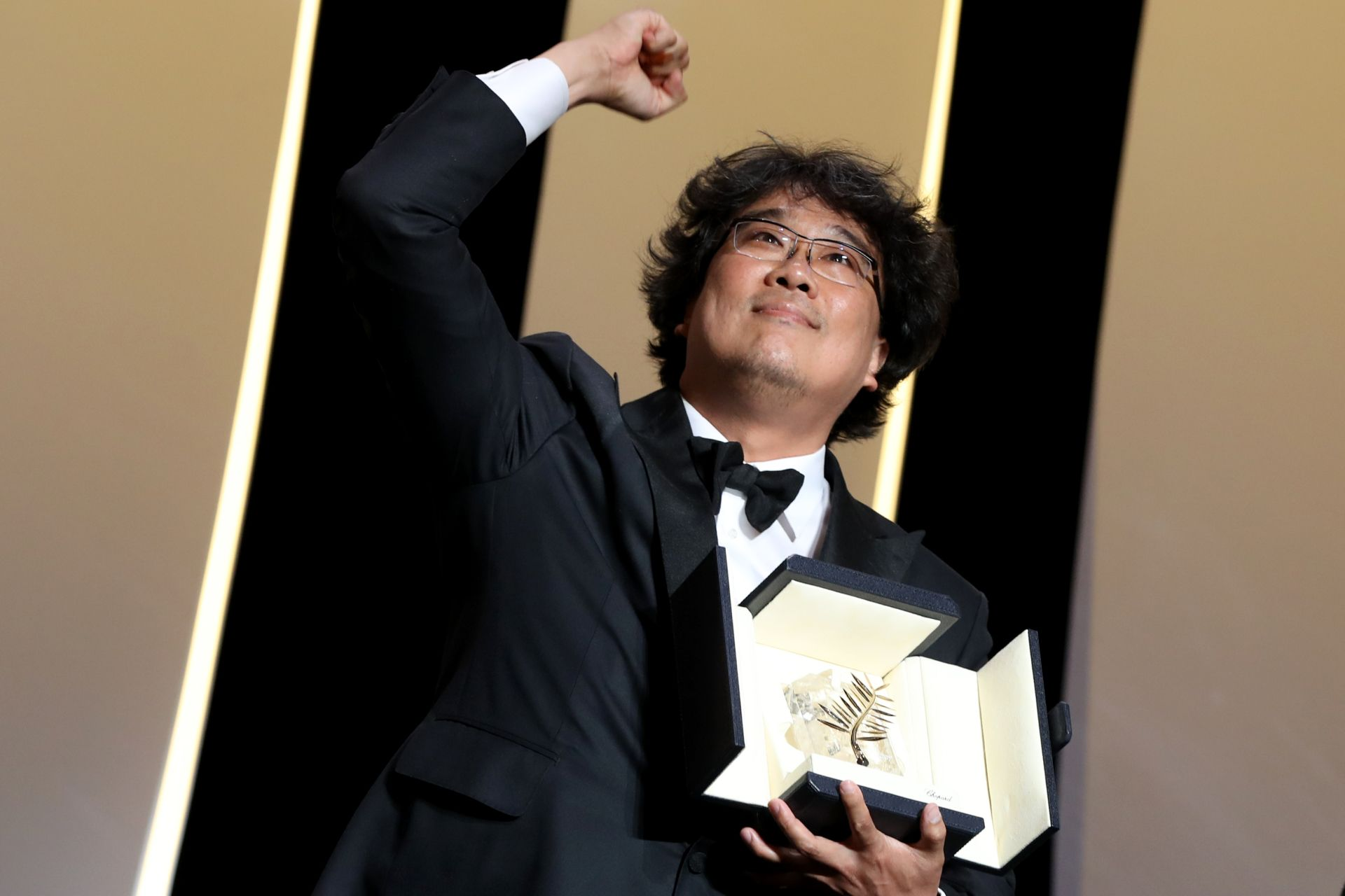 "South Korean director Bong Joon-Ho poses on stage with his trophy after he was awarded with the Palme d'Or for the film ""Parasite (Gisaengchung)"" on May 25, 2019 during the closing ceremony of the 72nd edition of the Cannes Film Festival in Cannes, southern France. (Photo by Valery HACHE / AFP)"