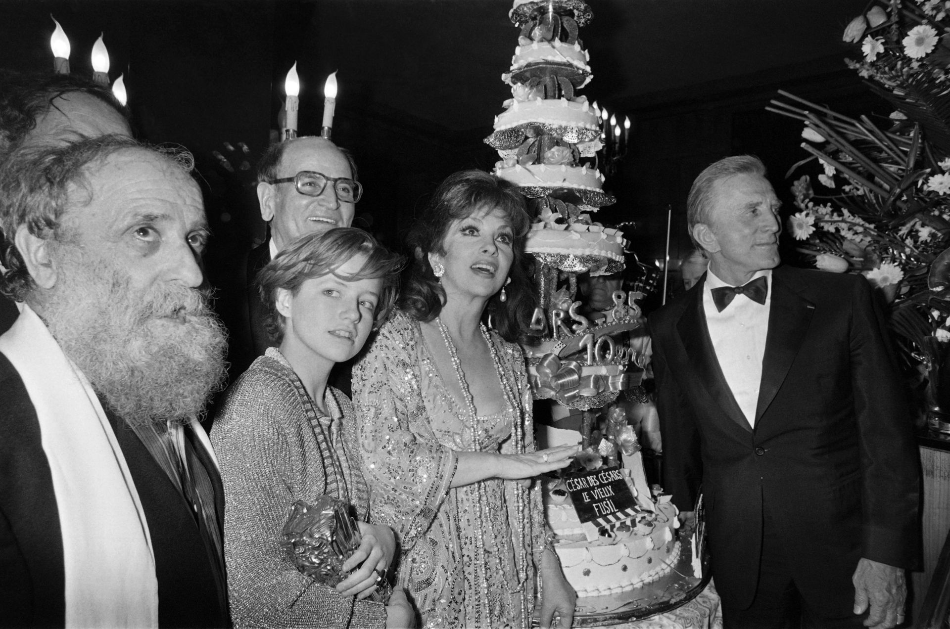 (from L), French sculptor Cesar, French actress Laure Marsac, Italian actress Gina Lollobrigida and US actor Kirk Douglas pose next to a cake to mark the 10th nuit des Cesar ceremony, on February 02, 1980, in Paris. Background, film producer Georges Cravenne.  AFP PHOTO JEAN-LOUP GAUTREAU / PIERRE VERDY (Photo by - / AFP)