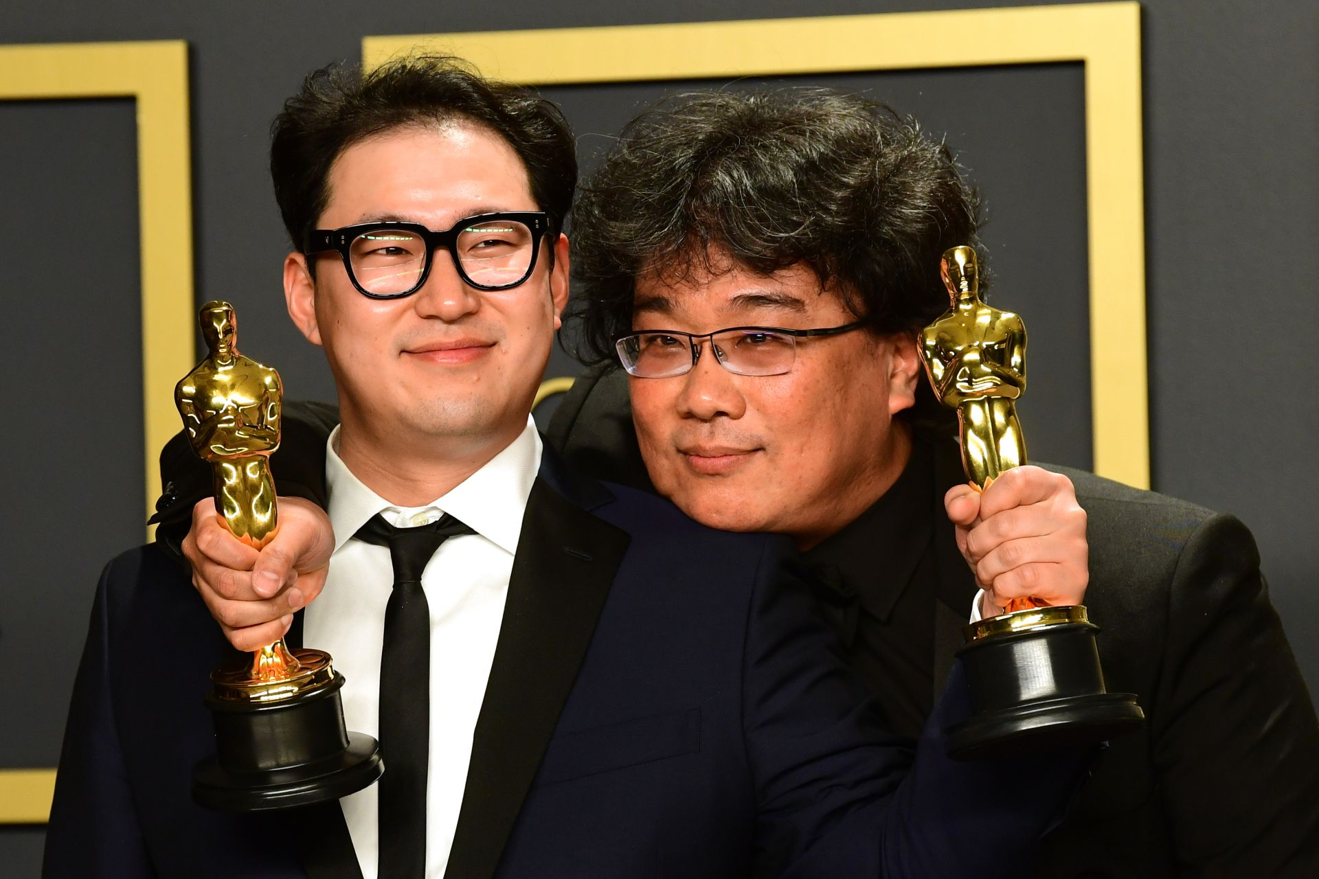 """Parasite"" writers Han Jin-won (L) and Bong Joon-ho pose in the press room with the Oscars for ""Parasite"" during the 92nd Oscars at the Dolby Theater in Hollywood, California on February 9, 2020. - Bong Joon-ho won for Best Director, Best Movie, Best International Feature Film and Best Original Screenplay for ""Parasite"". (Photo by FREDERIC J. BROWN / AFP)"