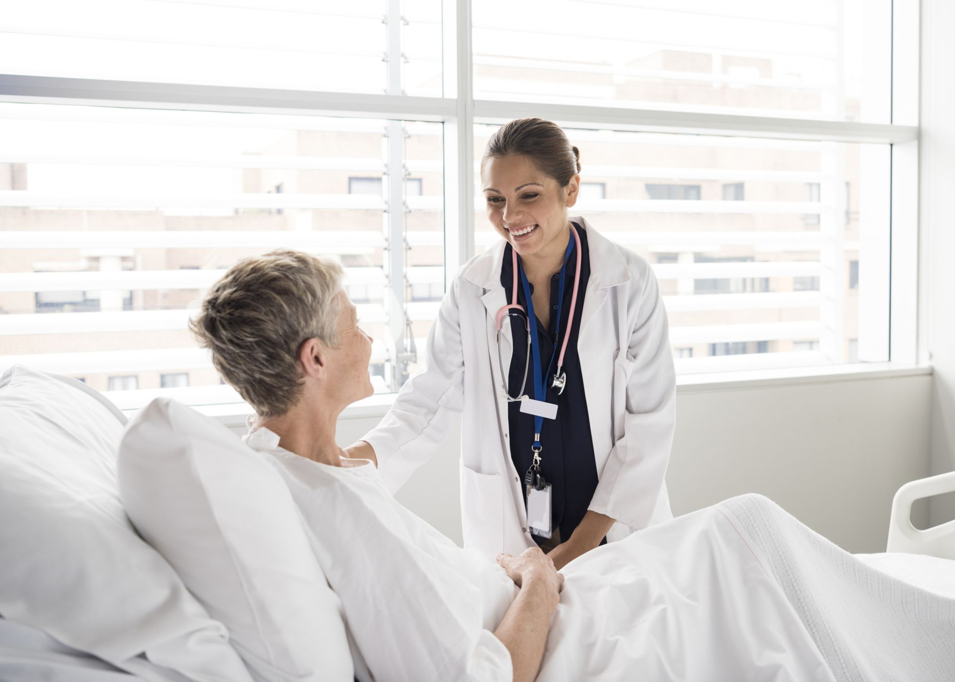 Senior woman in hospital bed listening to attractive female doctor. Medical professional caring for female patient in hospital bed.
