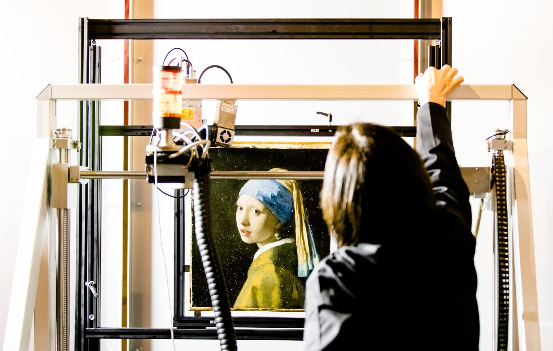 "(FILES) In this file photo taken on february 26, 2018 hows Johannes Vermeer's ""Girl with a Pearl Earring"" painting inside a XRF macro-scanner during a research at The Mauritshuis in The Hague. - New researches carried out on Vermeer's ''Girl with the Pearl Earring'', one of the most famous paintings in the world, has unveiled discoveries that makes it more 'personal' even if the identity of the woman still remains a mystery, announced the museum on April 28, 2020. (Photo by Bart MAAT / ANP / AFP) / Netherla"