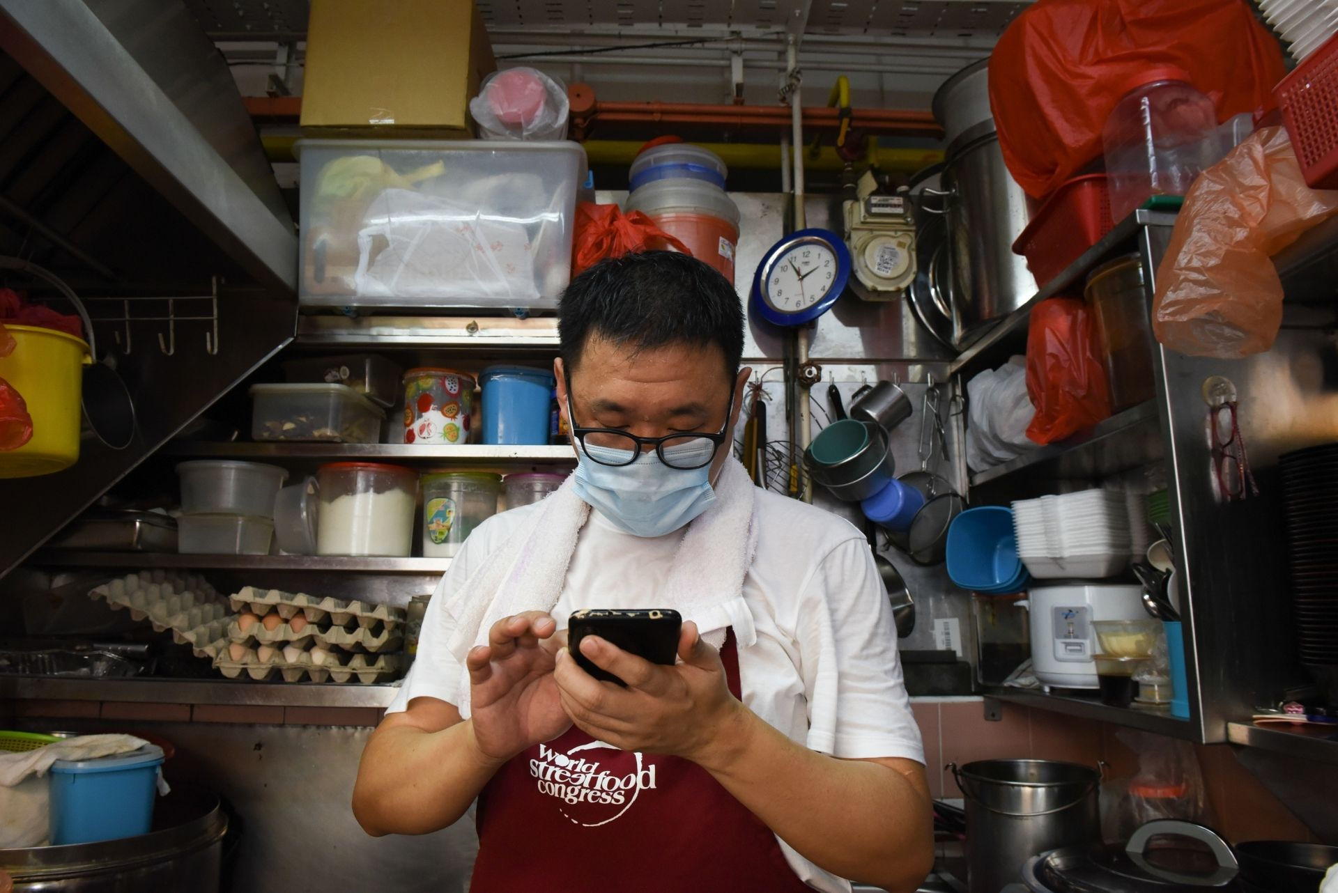This photo taken on April 21, 2020 shows Melvin Chew scrolling through his phone at his small food stall, as the business has moved to delivery only due to the COVID-19 coronavirus outbreak in Singapore. - From Facebook groups to hyper-local delivery services, Southeast Asia's street food chefs are cooking up creative ways to sell their wares as they struggle to survive amid the coronavirus pandemic. (Photo by Catherine LAI / AFP)