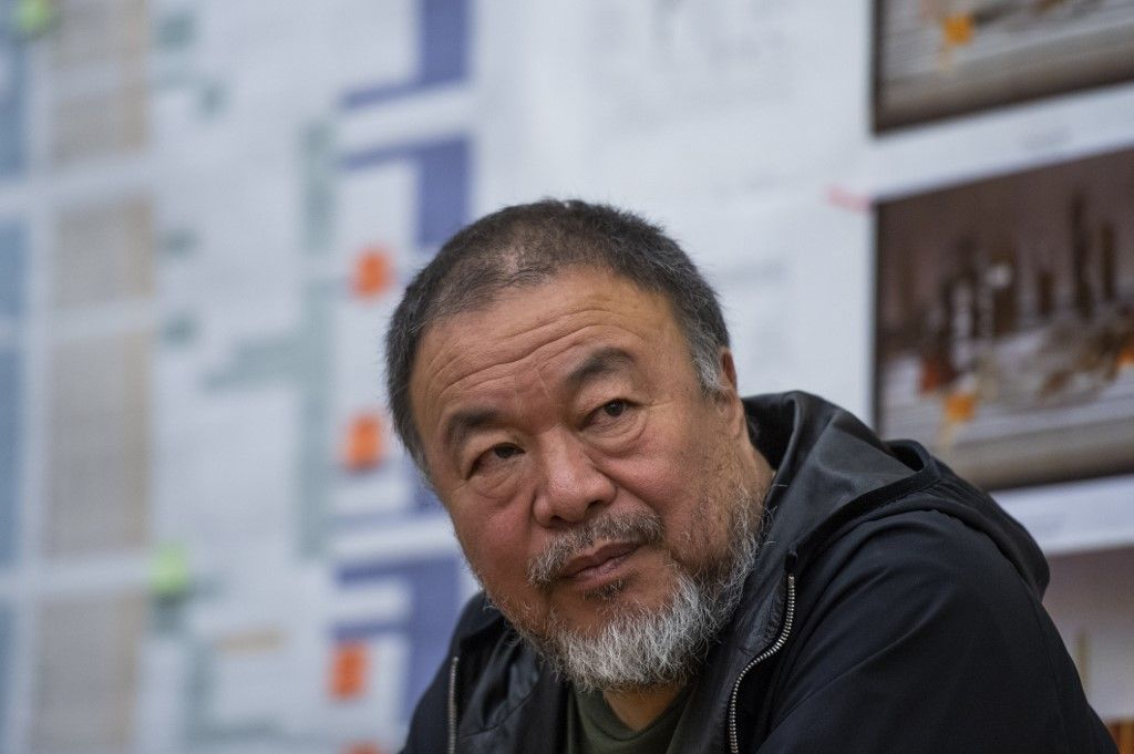 """Chinese dissident artist Ai Weiwei is pictured during an interview at the launch of his """"do-it-yourself"""" (DIY) art work """"Safety Jackets Zipped The Other Way"""", at his studio in Berlin on February 11, 2020. - The work, which is available in four different versions, consists of a set of high-visibility safety jackets zipped together to form a connected sculpture that can be made in different variations.  The project is sponsored by German home improvement giant Hornbach. (Photo by John MACDOUGALL / AFP)"""