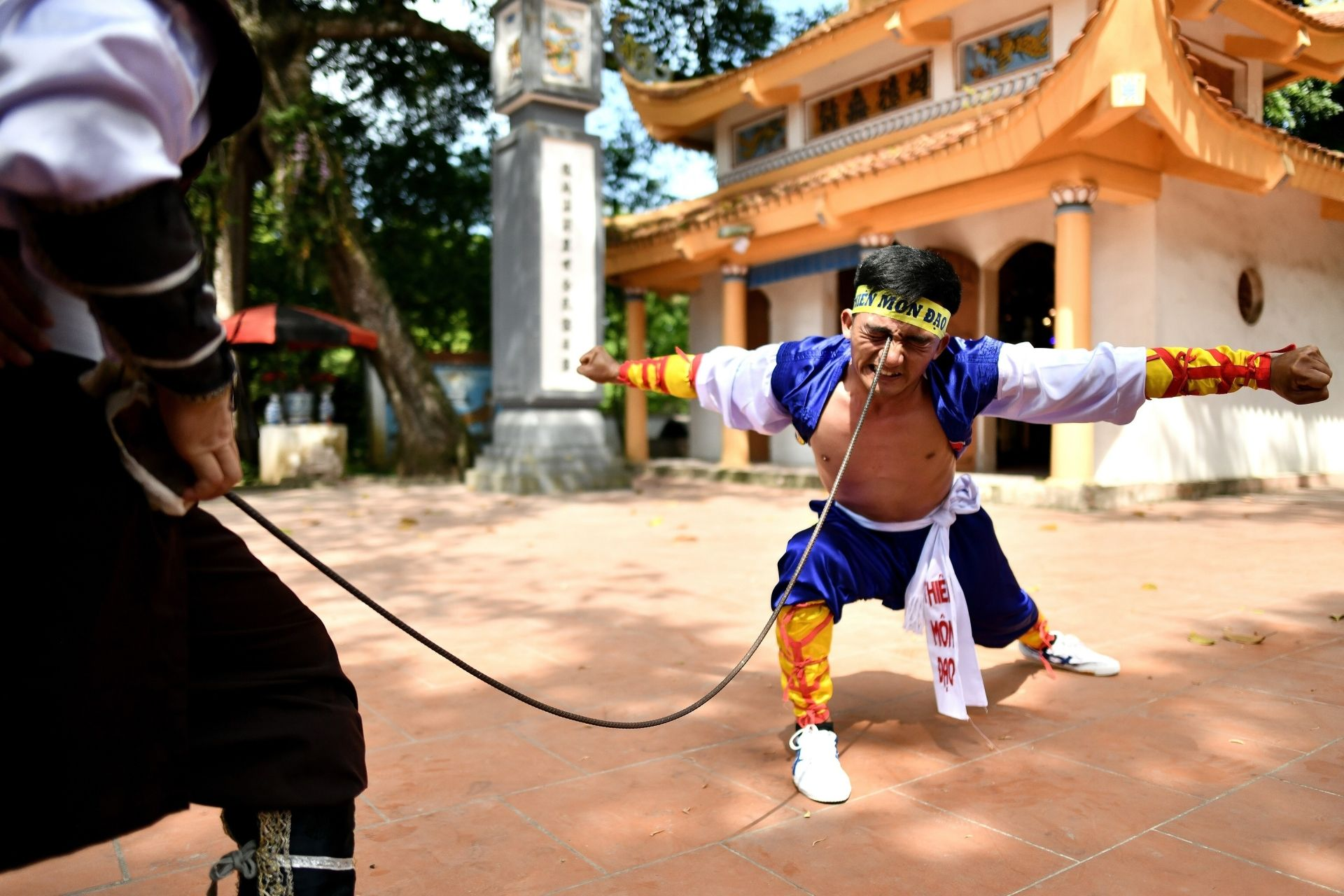 This photograph taken on June 7, 2020 shows Le Van Thang, 28, student of the centuries-old martial art of Thien Mon Dao, bending a construction rebar against his eye socket inside the Bach Linh temple compound at Du Xa Thuong village in Hanoi. - An increasing number of Vietnamese are finding refuge in the centuries-old martial art Thien Mon Dao, which grew out of a need to protect the country from invaders but now offers a route to mental wellbeing in the rapidly changing Communist nation. (Photo by Manan V