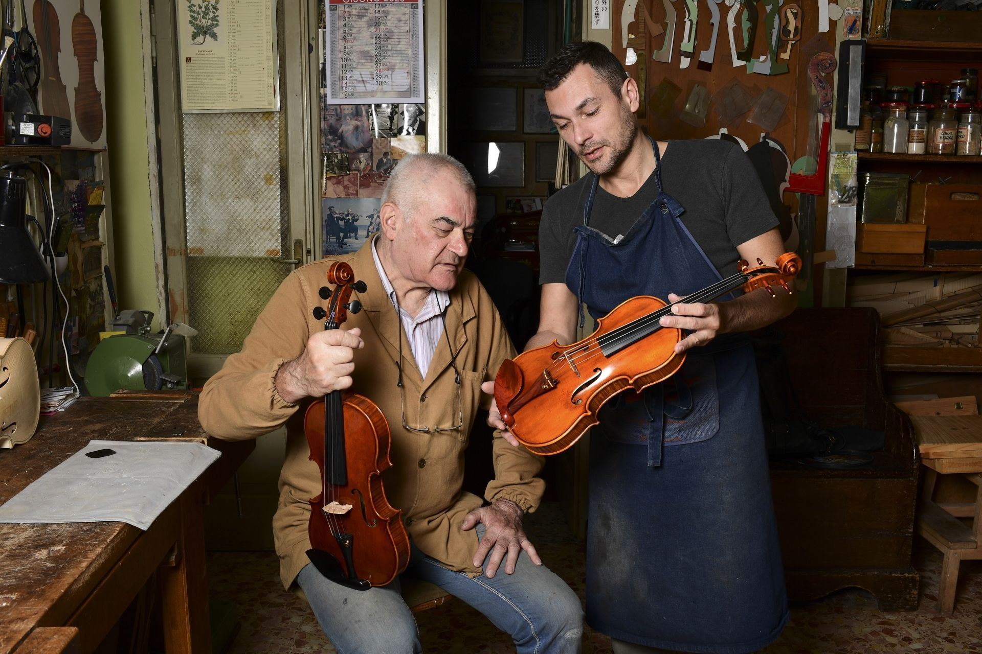 Cremona's current oldest luthier, Hungary's Stefano Conia (74) and his son Stefano Jr (47) are pictured with a violin at their workshop in Cremona on June 9, 2020. - Stradivarius' homeland, the Italian city of Cremona, has become a laboratory for luthiers from all over the world : working in the tradition of the great masters, they try to resist despite a shrinking market and fierce Chinese competition. (Photo by Miguel MEDINA / AFP)