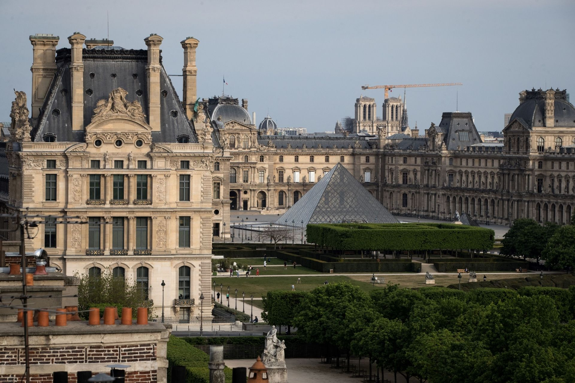 This picture shows the pyramid of The Louvre Museum designed by Ieoh Ming Pei, The Louvre Museum, part of the Tuileries garden and the Notre-Dame de Paris cathedral (background) on April 21, 2020 in Paris, as the country is under lockdown to stop the spread of the Covid-19 pandemic caused by the novel coronavirus. (Photo by JOEL SAGET / AFP)