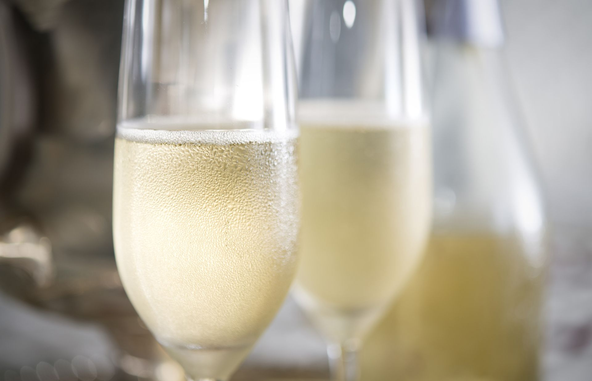 Closeup of two flutes of champagne with bubbles and droplets of condensation with silver ice bucket and bottle in background.
