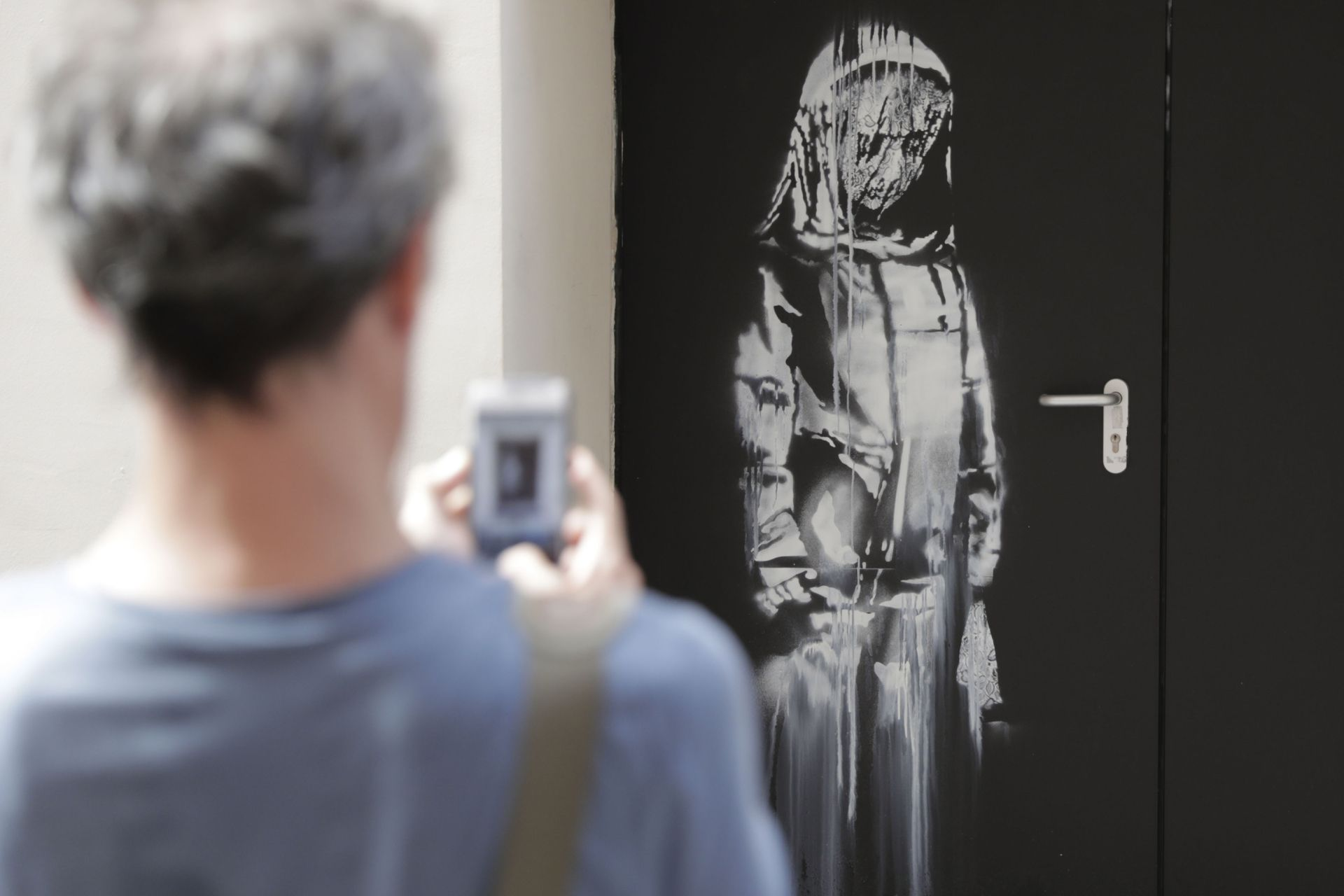 A man takes a photograph of a recent artwork by street artist Banksy in Paris on June 25, 2018, on a side street to the Bataclan concert hall where a terrorist attack killed 90 people on Novembre 13, 2015. - The mysterious British street artist has created a series of new murals in Paris in the last few days. (Photo by Thomas SAMSON / AFP)
