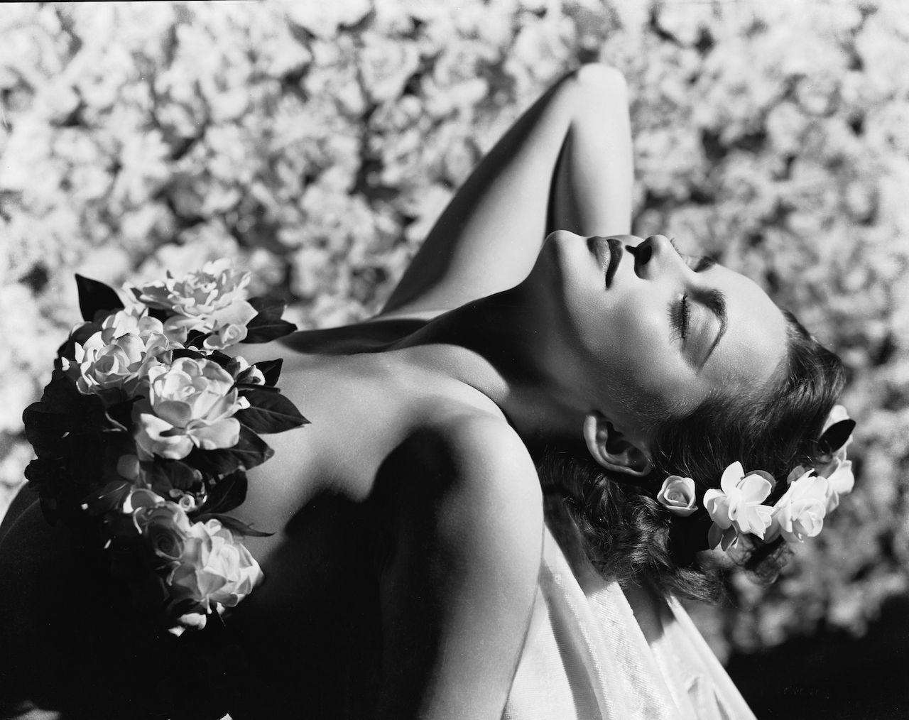 1938:  British-born actress Olivia de Havilland adorned with flowers.  (Photo via John Kobal Foundation/Getty Images)