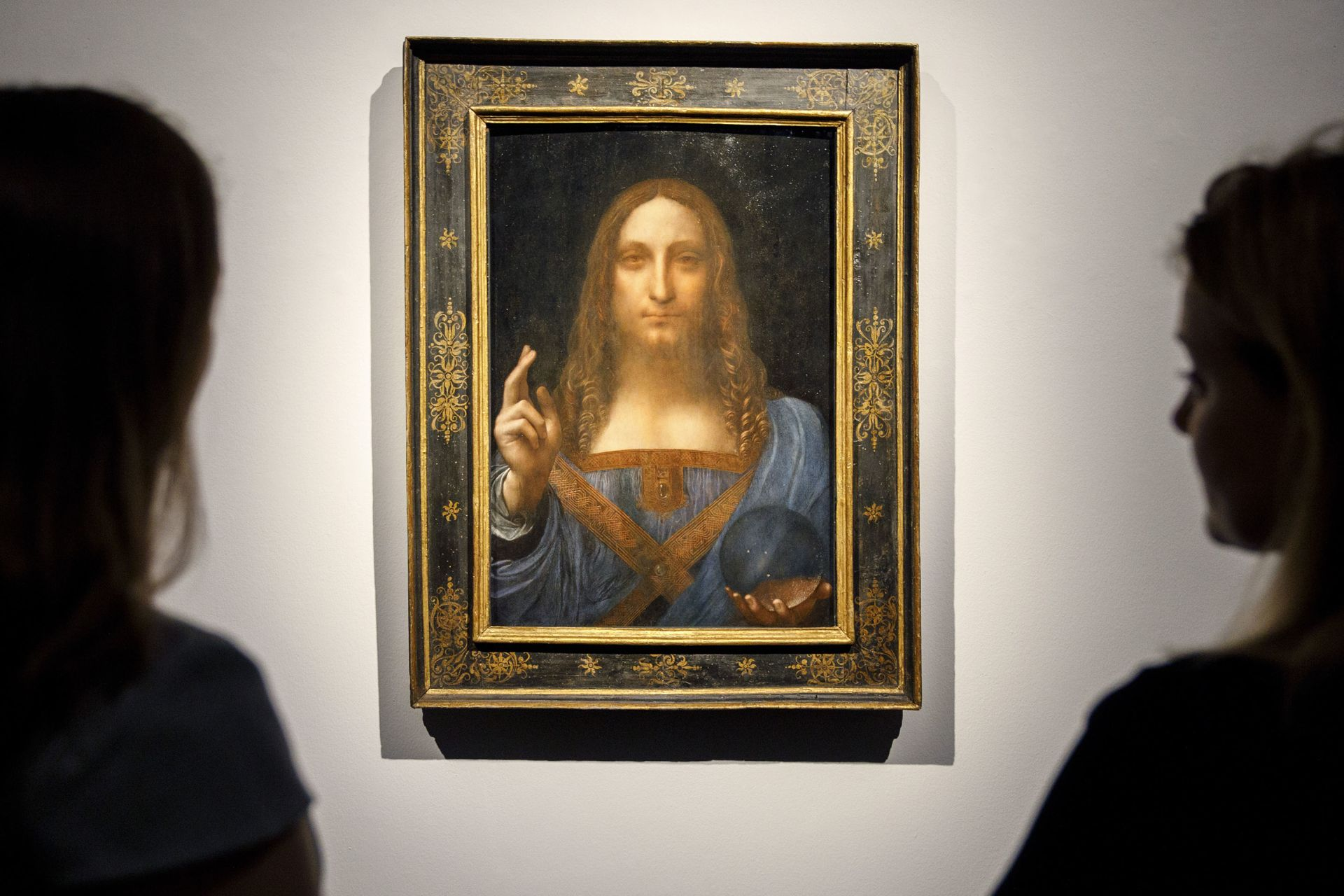 """In this file photo taken on October 24, 2017 Christie's employees pose in front of a painting entitled Salvator Mundi by Italian polymath Leonardo da Vinci at a photocall at Christie's auction house in central London.The Louvre Abu Dhabi said on June 27, 2018 it will unveil its most prized acquisition to date, a Leonardo da Vinci painting that sold for nearly half a billion dollars at auction, on September 18. The 500-year-old """"Salvator Mundi"""" painting depicting Jesus Christ, believed to be the wor"""