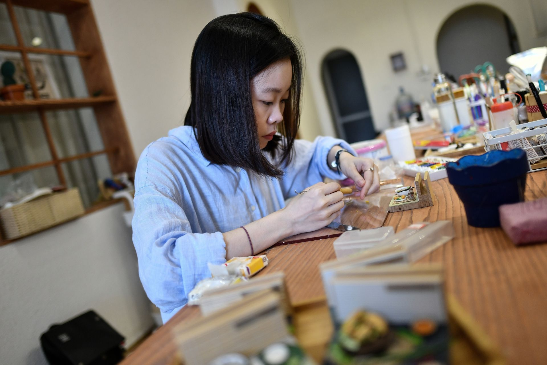 This photograph taken on August 18, 2020 shows miniature artist Nguyen Thi Ha An working at her studio in Hanoi. - An -- a 28-year-old architecture graduate -- began crafting food miniatures made from clay a year ago, spotting a chance to capitalise on the world's growing love for Vietnamese cuisine. (Photo by Manan VATSYAYANA / AFP)