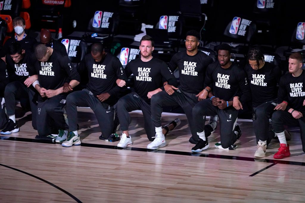 LAKE BUENA VISTA, FL - JULY 31: Players kneel and wear Black Lives Matter shirts before the start of an NBA basketball game between the Milwaukee Bucks and the Boston Celtics. (Photo by Ashley Landis-Pool/Getty Images)