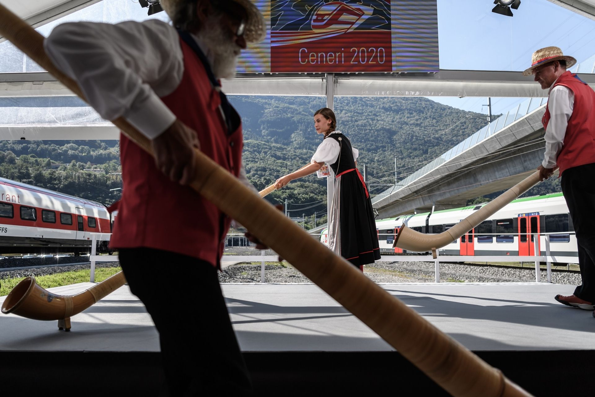 Alphorn blowers arrive on stage on September 4, 2020, in Camorino, southern Switzerland during the inauguration of the Ceneri Base railway tunnel, a two single-track 15,4 km long tunnel final part of the New Railway Link through the Alps (NRLA) construction project by Swiss autorities for faster rail links across the Alps aiming to mainly reduce transalpine truck traffic. - The rail service is expected to start in December 2020. (Photo by Fabrice COFFRINI / AFP)