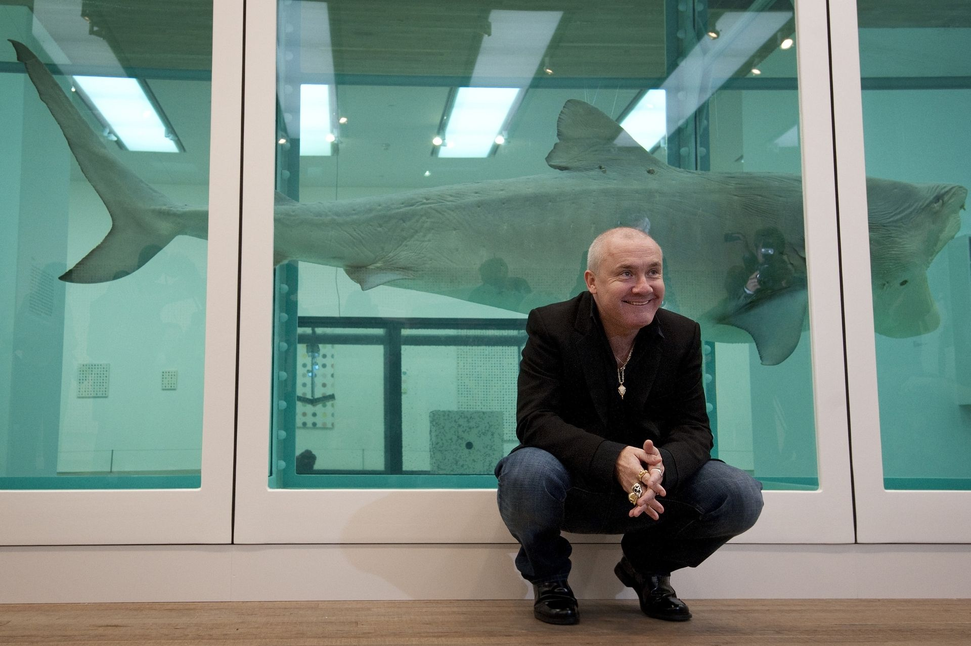 British artist Damien Hirst poses for photographers next to his 1991 work 'The Physical Impossibility of Death in the Mind of Someone Living' during the opening of his solo exhibition showcasing work spanning over two decades at the Tate Modern in central London on April 2, 2012. AFP PHOTO / BEN STANSALL (Photo by BEN STANSALL / AFP)