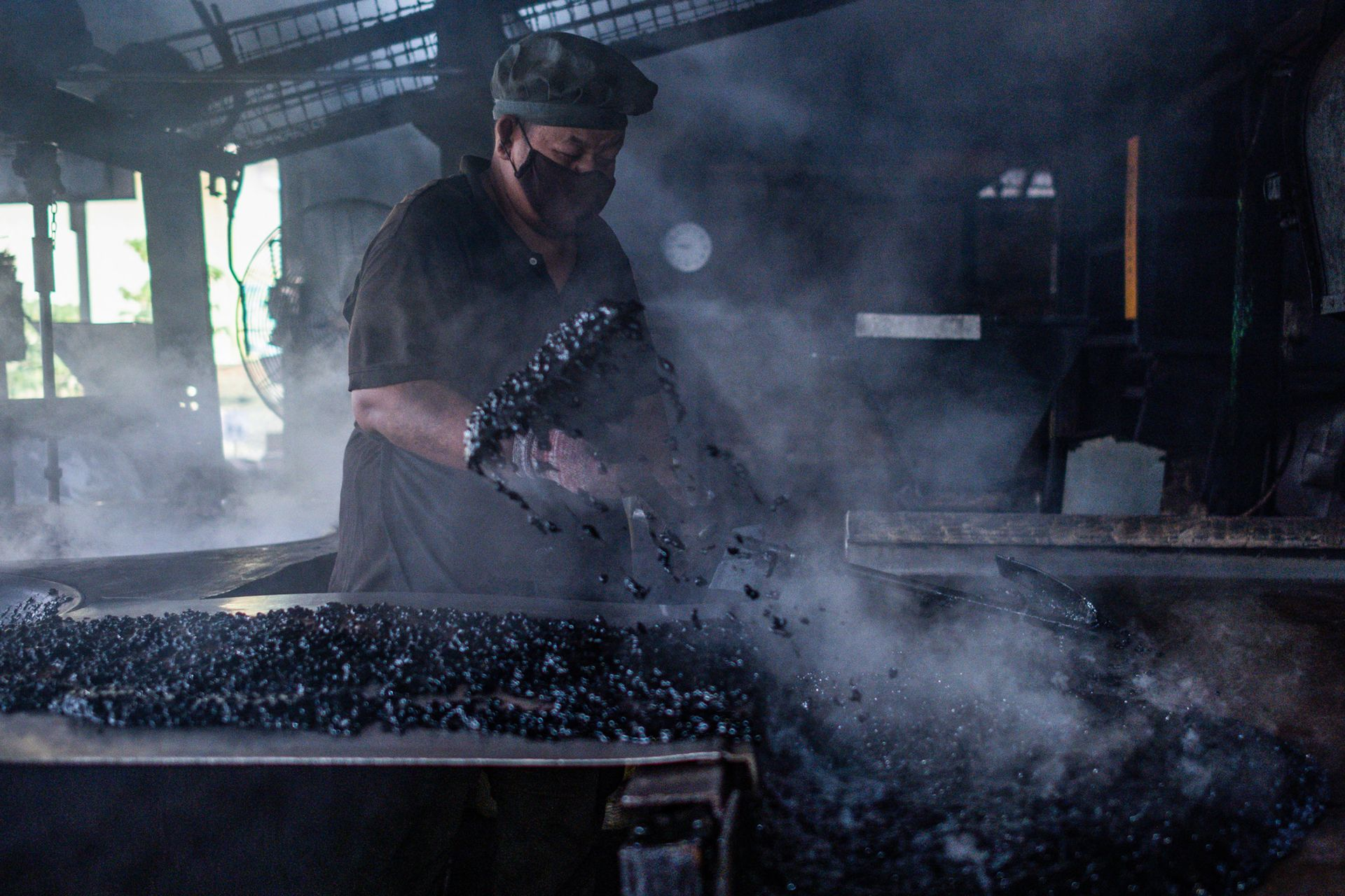 This picture taken on September 29, 2020 shows a worker transferring pre-sweetened black coffee for cooling at the Antong Coffee Factory in Taiping in the Malaysian state of Perak. - In the town of Taiping in central Perak state, the Antong coffee mill has been using antique machines and traditional bean-roasting methods to produce its famed caffeine-laden powder for 87 years. (Photo by Mohd RASFAN / AFP) / To go with AFP story Malaysia-food-drink-coffee