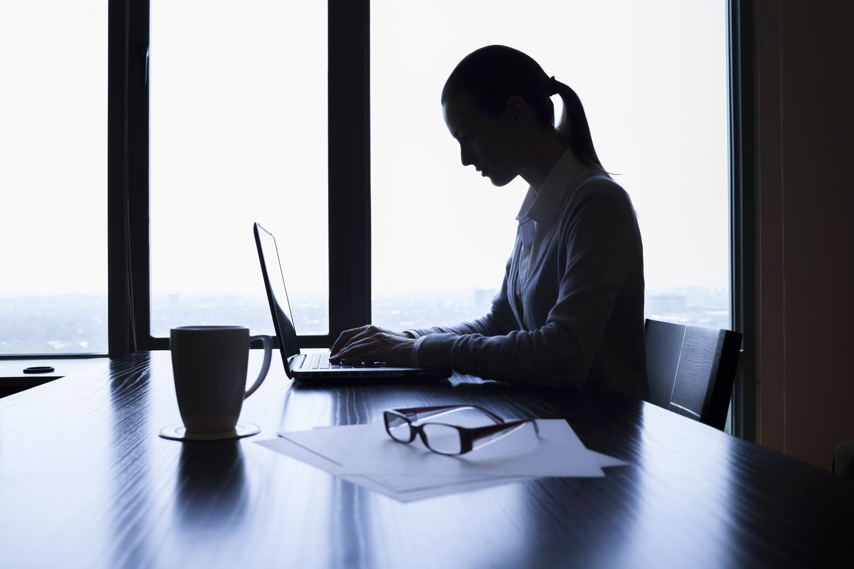 Silhouette of businesswoman using laptop computer in the office.