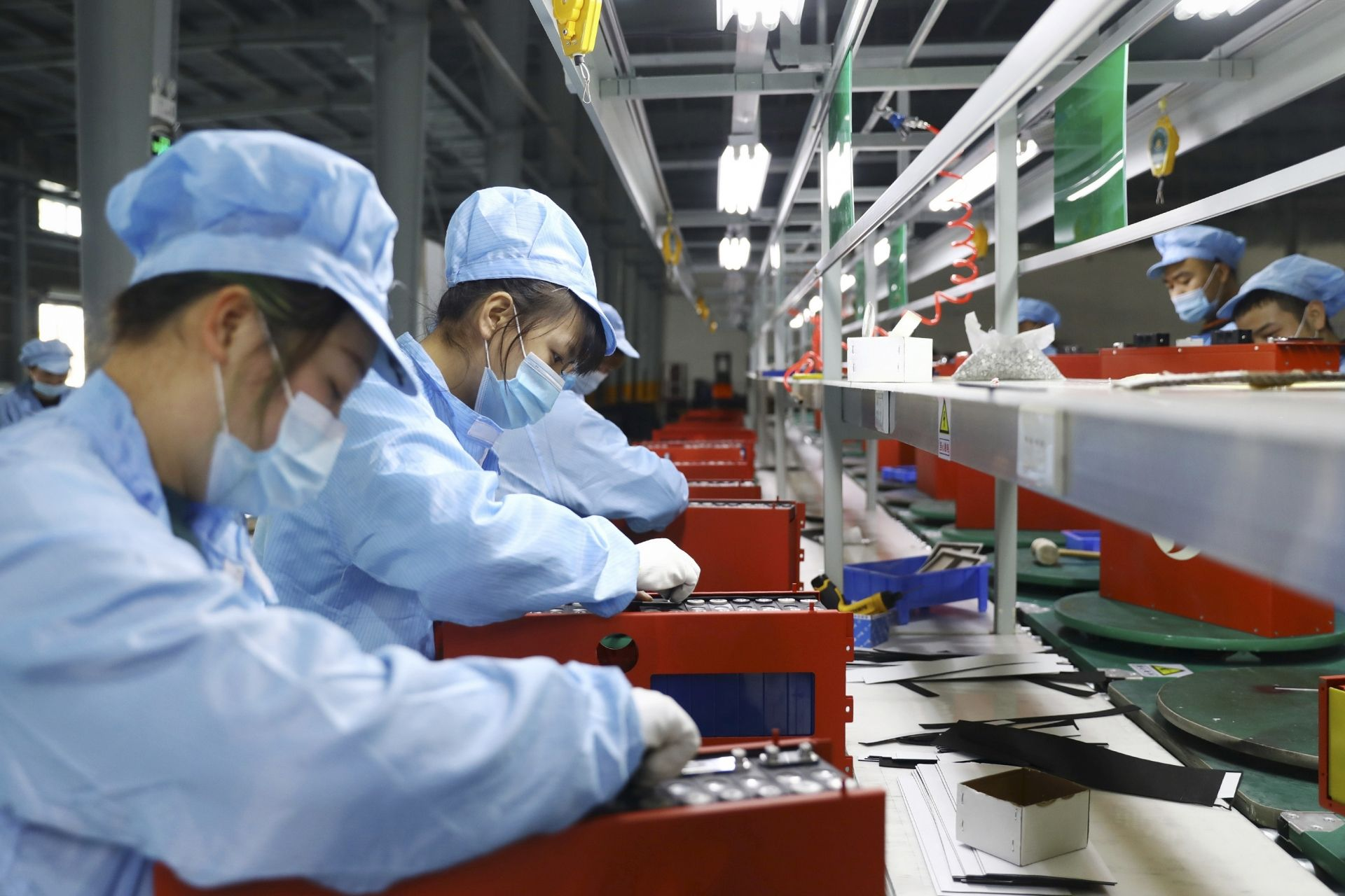 This photo taken on November 14, 2020 shows employees working in the workshop of a lithium battery manufacturing company in Huaibei, eastern China's Anhui province. (Photo by STR / AFP) / China OUT
