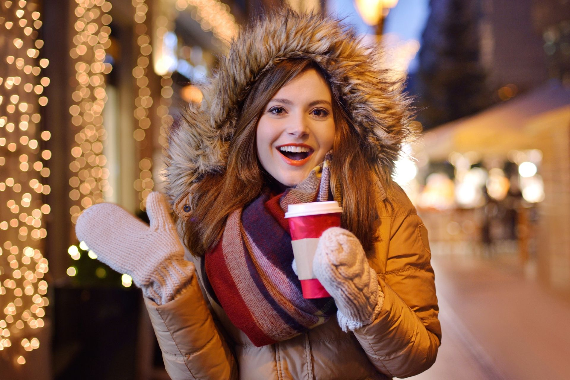 Young woman drinking coffee / tea in a Christmas fare.