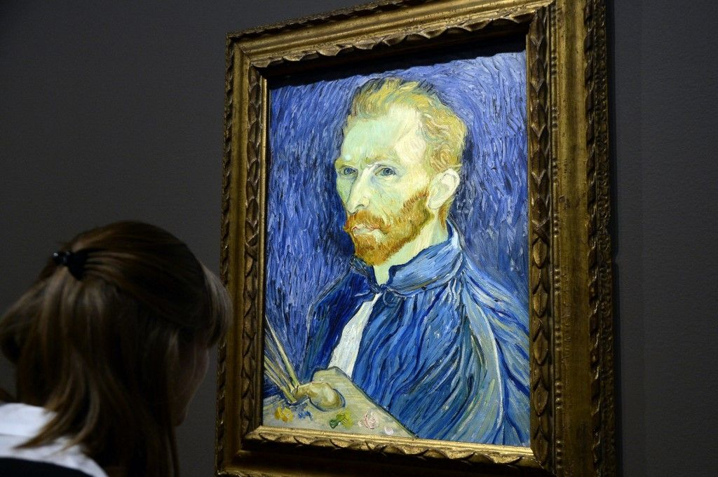 """A visitor looks at  a self-portrait by  late Dutch painter Vincent Van Gogh displayed at the Orsay Museum as part of the exhibition """"Van Gogh/Artaud. The Man Suicided by Society"""", on March 10, 2014 in Paris. AFP PHOTO / BERTRAND GUAY (Photo by BERTRAND GUAY / AFP)"""