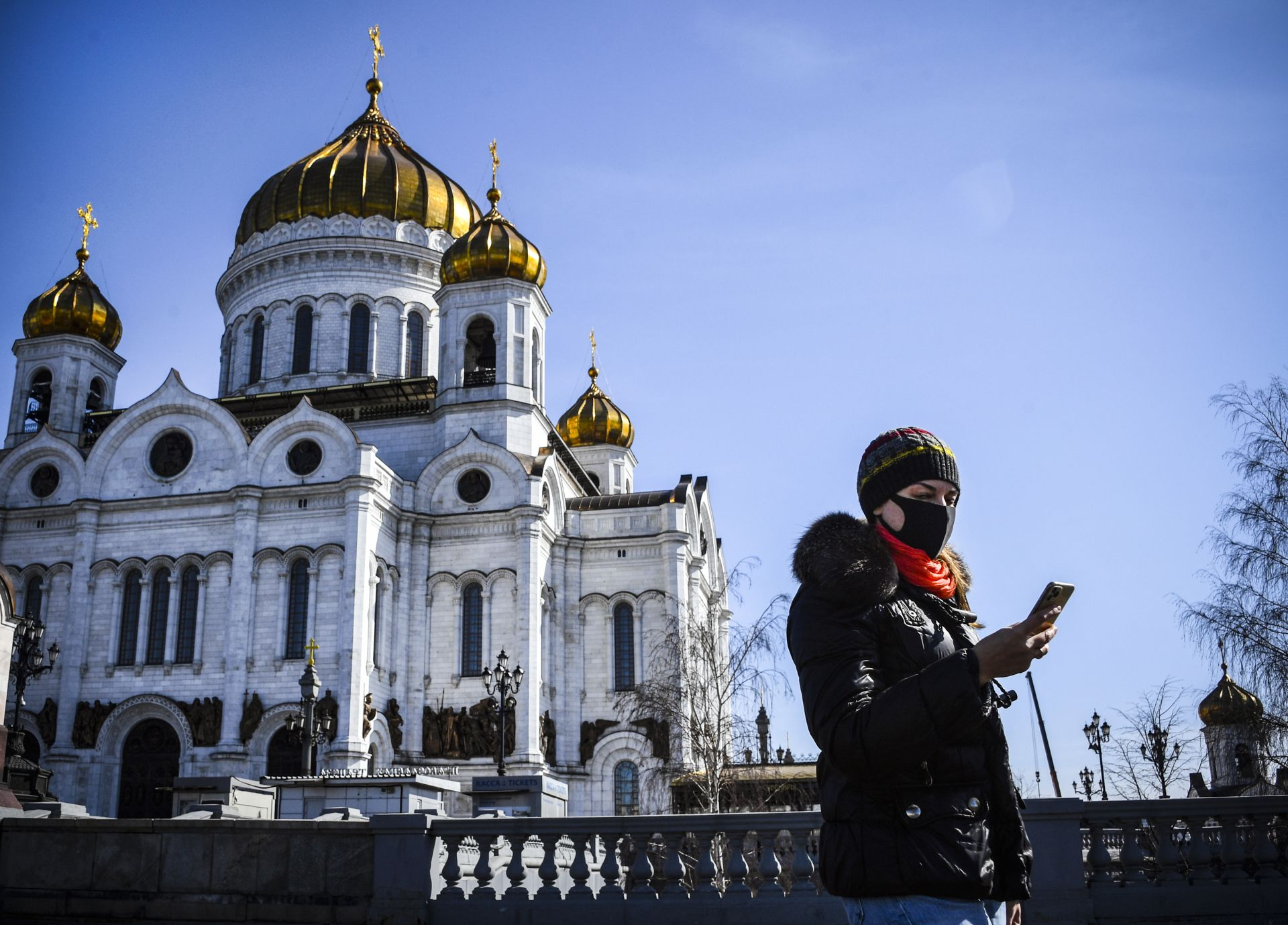 A woman wearing a face mask, amid concerns over the spread of the COVID-19 coronavirus, walks past the Cathedral of Christ the Saviour in downtown Moscow on March 26, 2020. (Photo by Alexander NEMENOV / AFP)