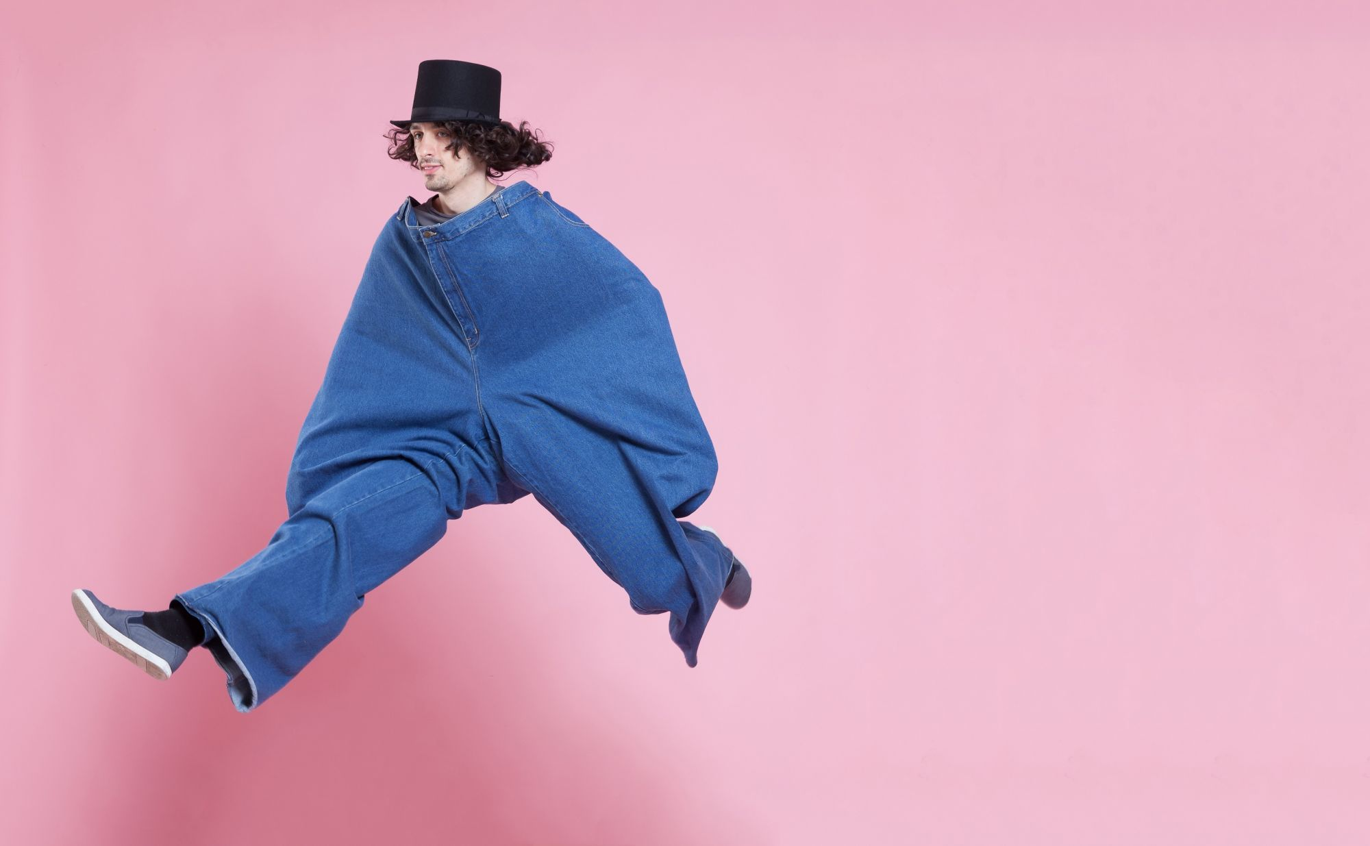 Young man wearing extra large pants and a top hat, jumping high.