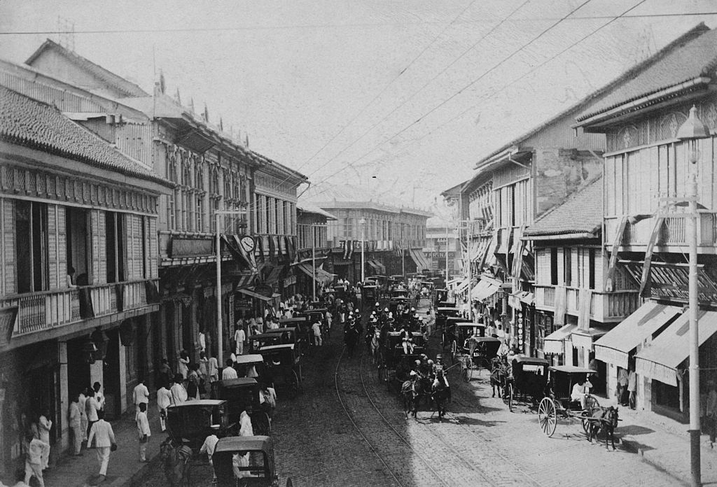 The Archbishop's carriage passes down La Escolta, the main street of Manila in the Philippines, circa 1910. (Photo by Rischgitz/Hulton Archive/Getty Images)
