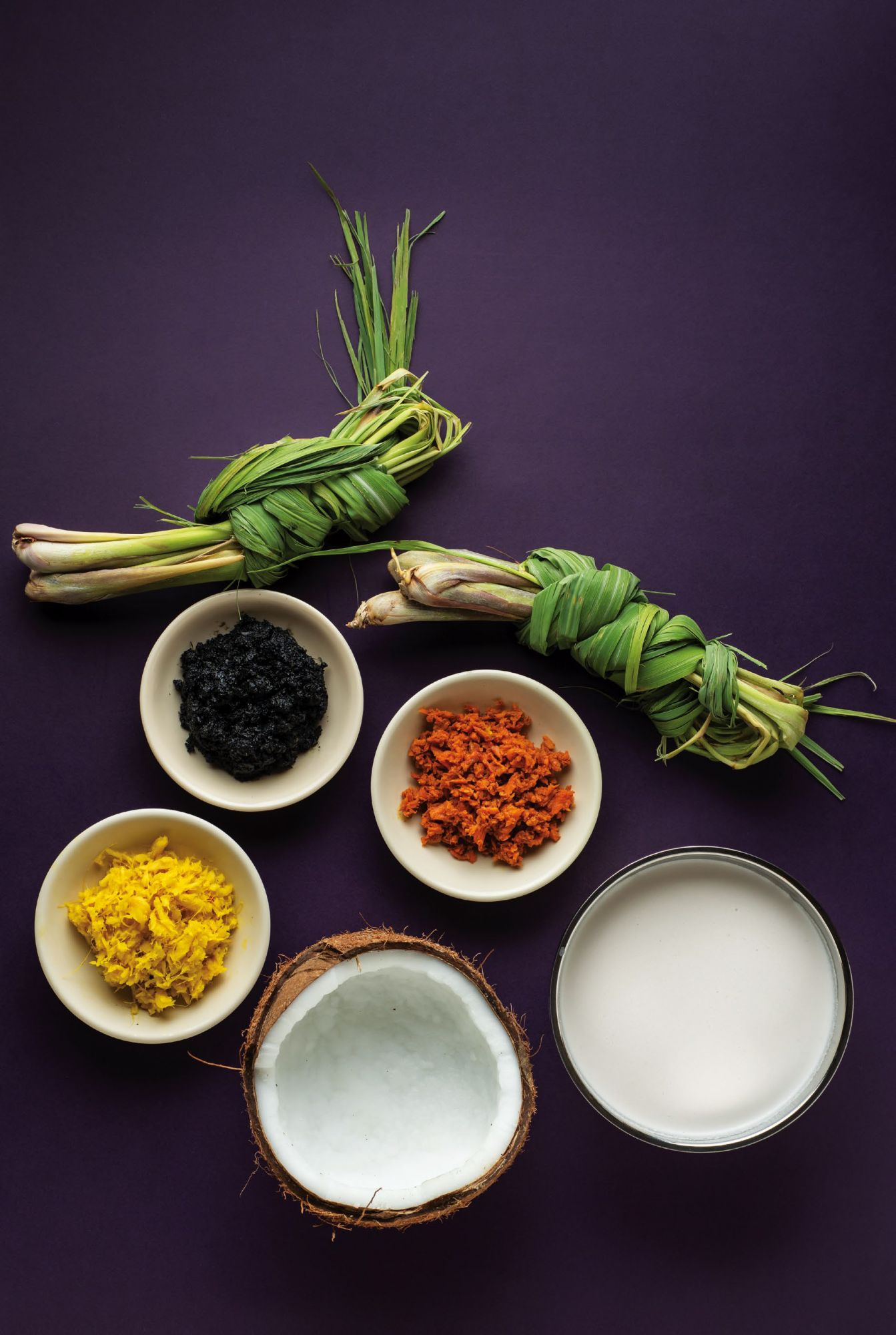 Staple spices and ingredients in a Muslim kitchen: (anticlockwise) lemongrass, ground turmeric, pamapa itum, crushed ginger, coconut oil in half a husk, coconut milk