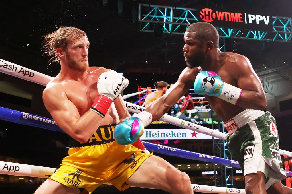 MIAMI GARDENS, FLORIDA - JUNE 06: Floyd Mayweather (R) exchanges blows with Logan Paul during their contracted exhibition boxing match at Hard Rock Stadium on June 06, 2021 in Miami Gardens, Florida. (Photo by Cliff Hawkins/Getty Images)