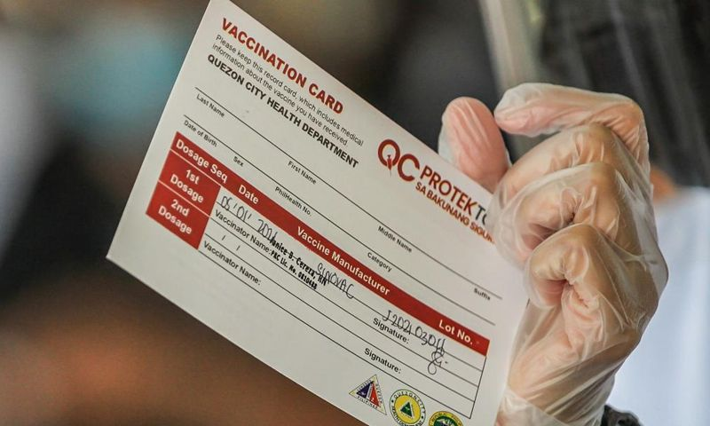 A health worker shows a vaccination card before giving a dose of the Sinovac COVID-19 vaccine to resident in Manila, the Philippines on May 1, 2021. | Photo: Xinhua
